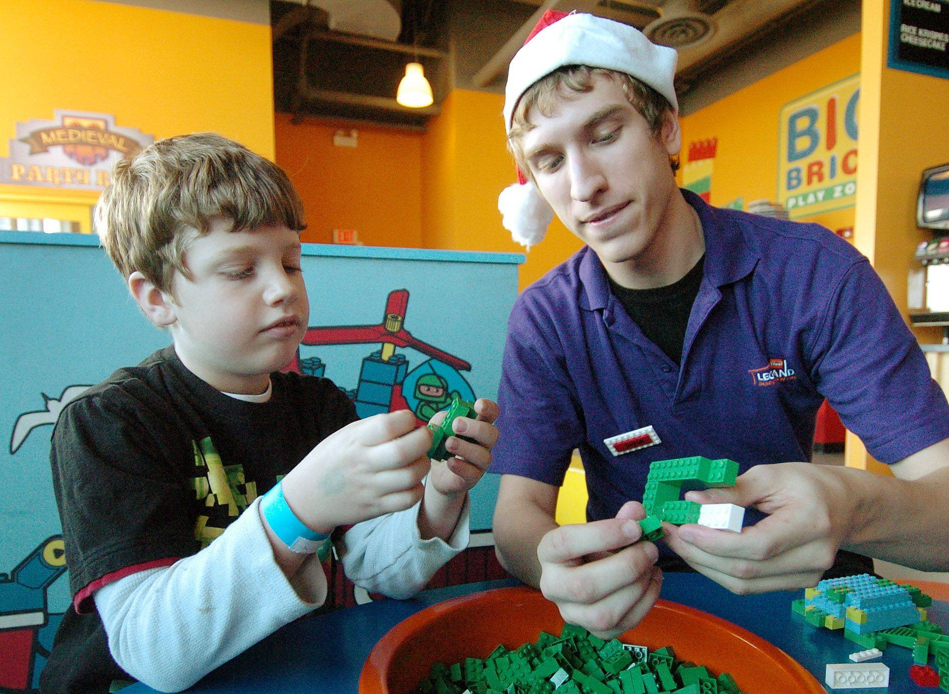 Nine-year-old Jacob Roscizewski of Franklin, Wisconsin builds Christmas ornaments out of LEGOs with employee Chris Sliga on the first day of Holiday Workshops at Legoland in the Streets of Woodfield in Schaumburg.