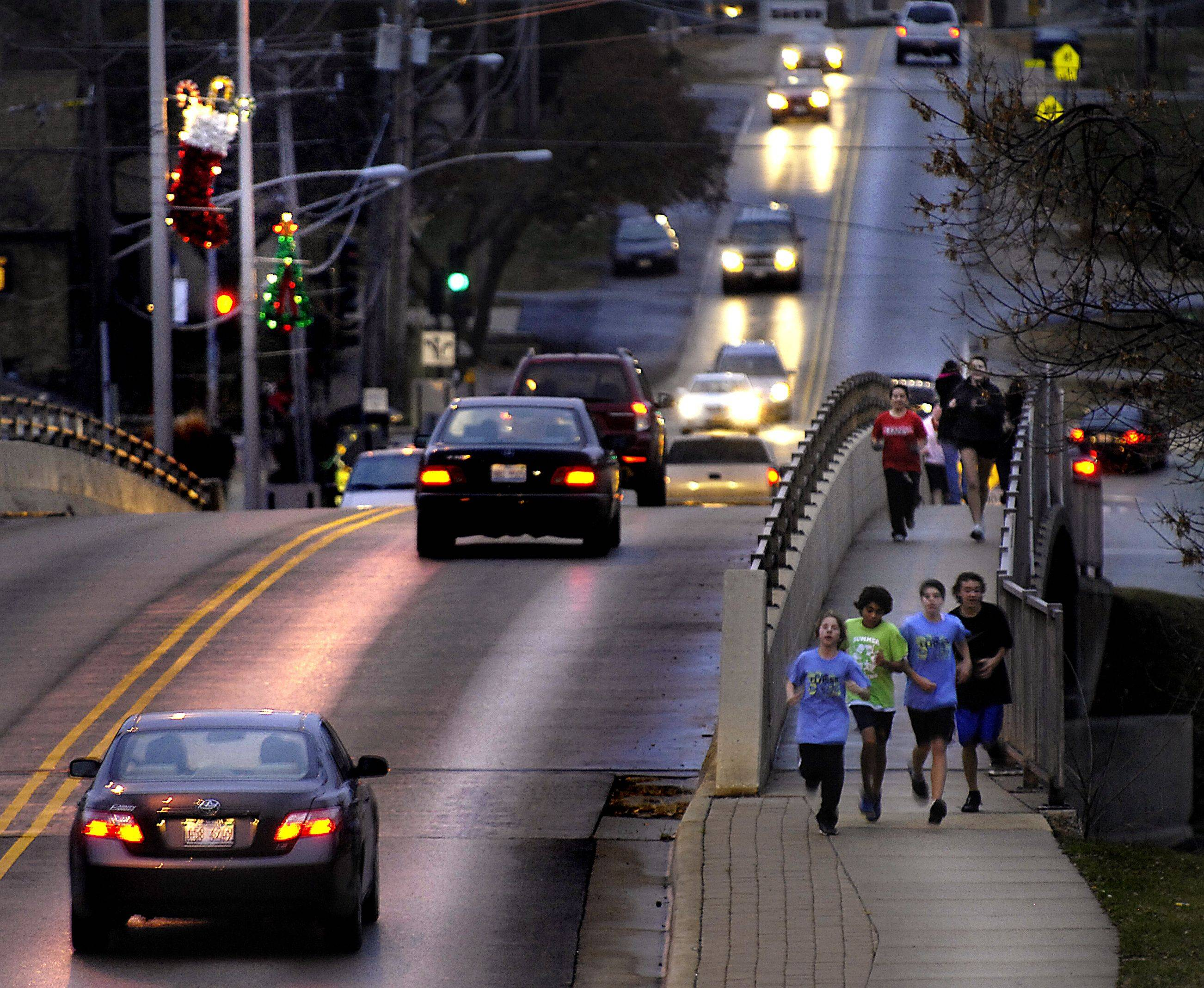 South Elgin High School athletes run across the Fox River bridge Monday afternoon on a training run.