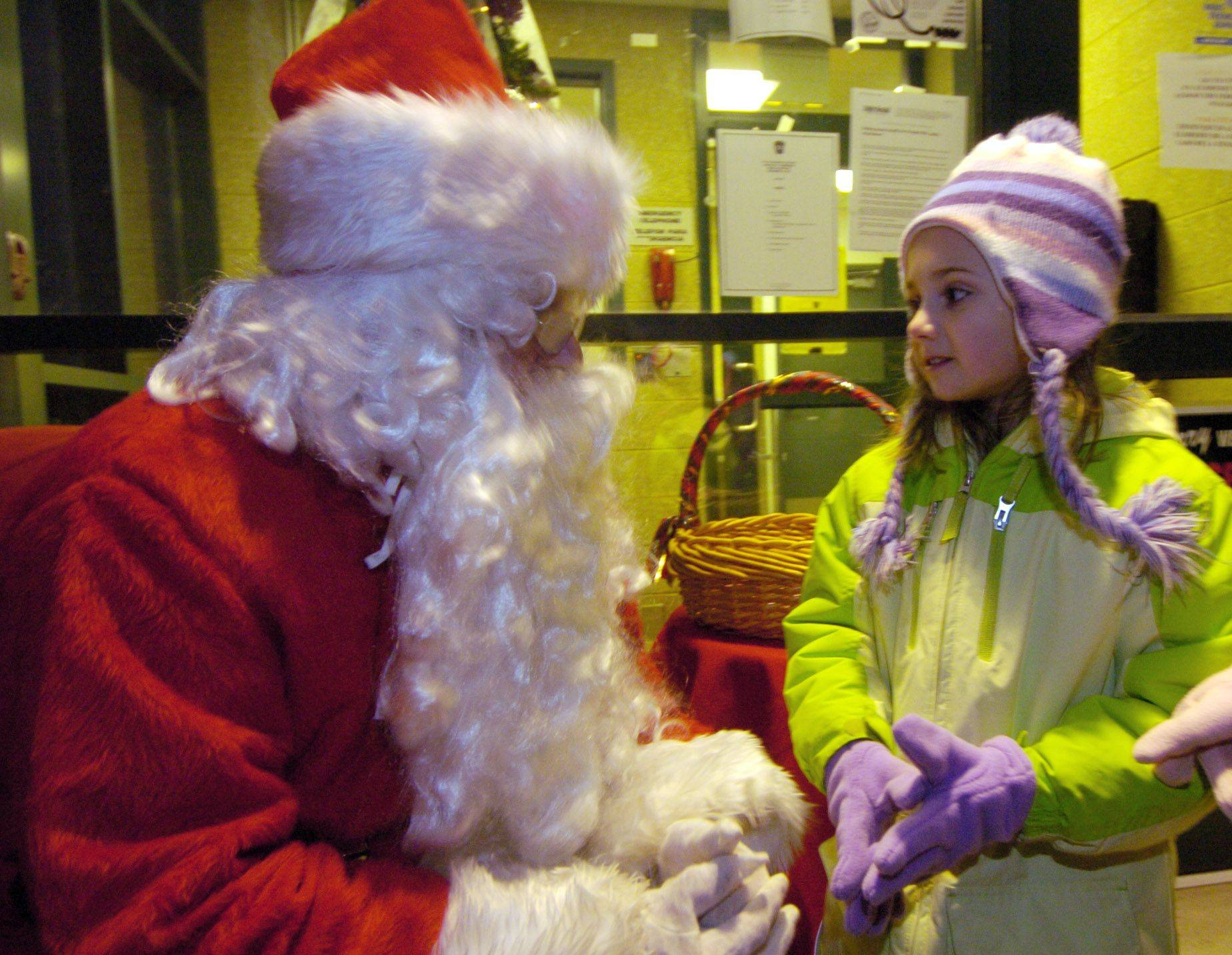 Kayla Nelesen, 6, of Gurnee visits with Santa Saturday evening in Prospect Heights while attending the tree lighting ceremony with her grandmother.