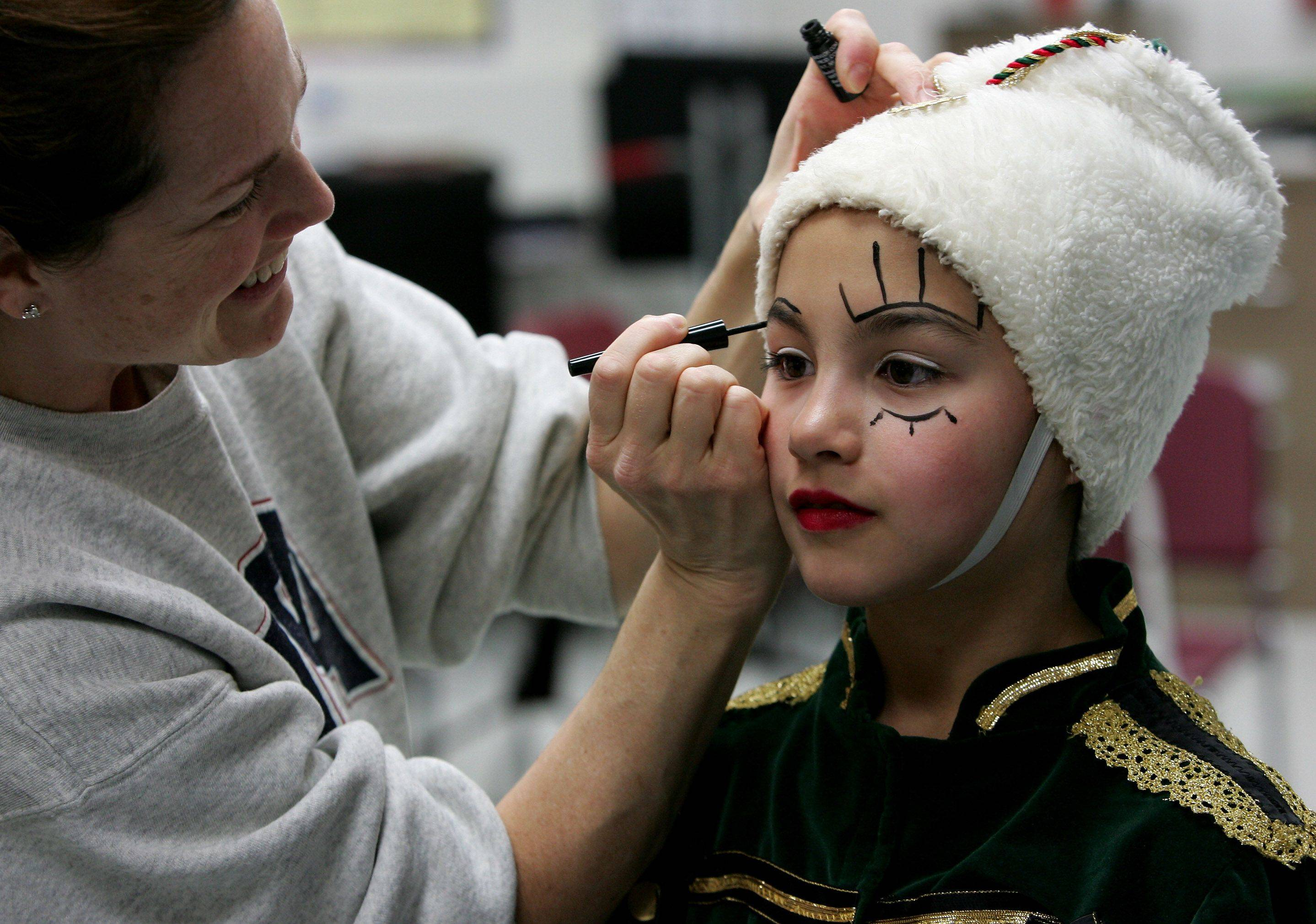 "Dianna Conlon of Gurnee applies makeup to her daughter, Maura, 9, who plays a part in ""The Magic of the Nutcracker"" presented by the Dancenter North beginning Saturday at Libertyville High School."