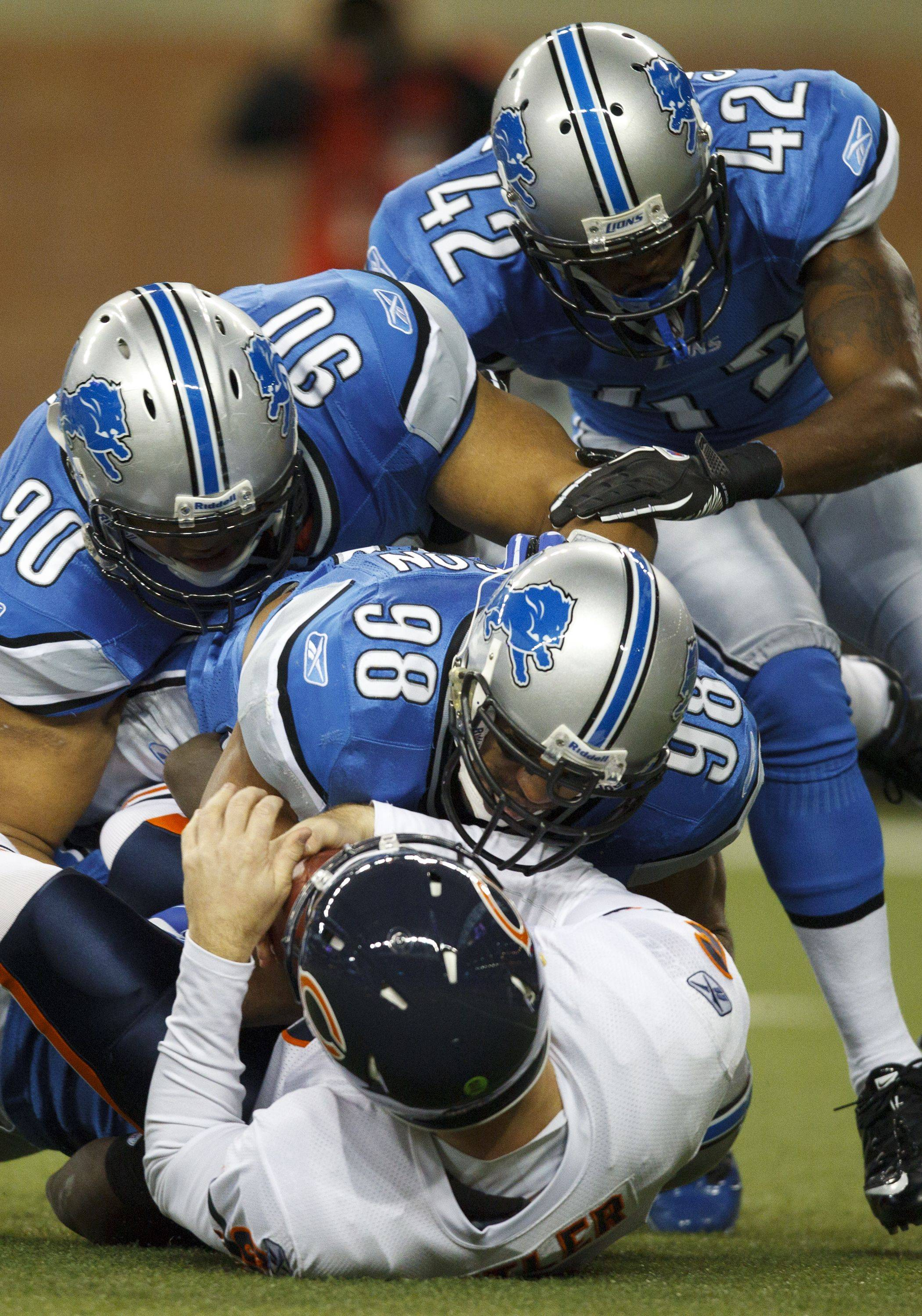 Detroit Lions defensive tackle Ndamukong Suh, Detroit Lions linebacker Julian Peterson and Detroit Lions cornerback Amari Spievey sack Chicago Bears quarterback Jay Cutler in the first half.