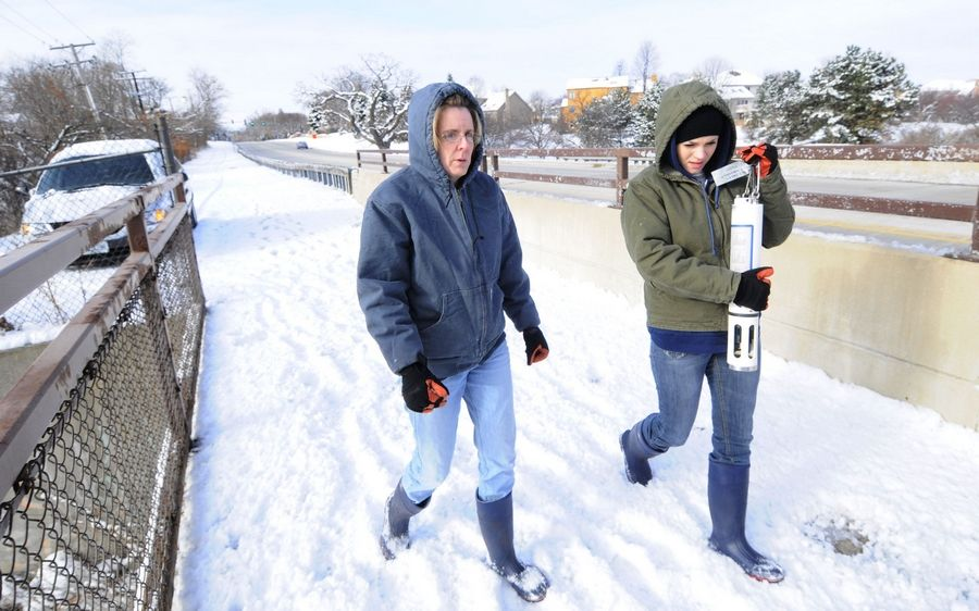 Downers Grove Sanitary District Lab Supervisor Mary Dressel, left, and lab analyst Malwina Serpa carry an instrument to a bridge on the East Branch of the DuPage River to measure the amount of salt in the river during the winter.