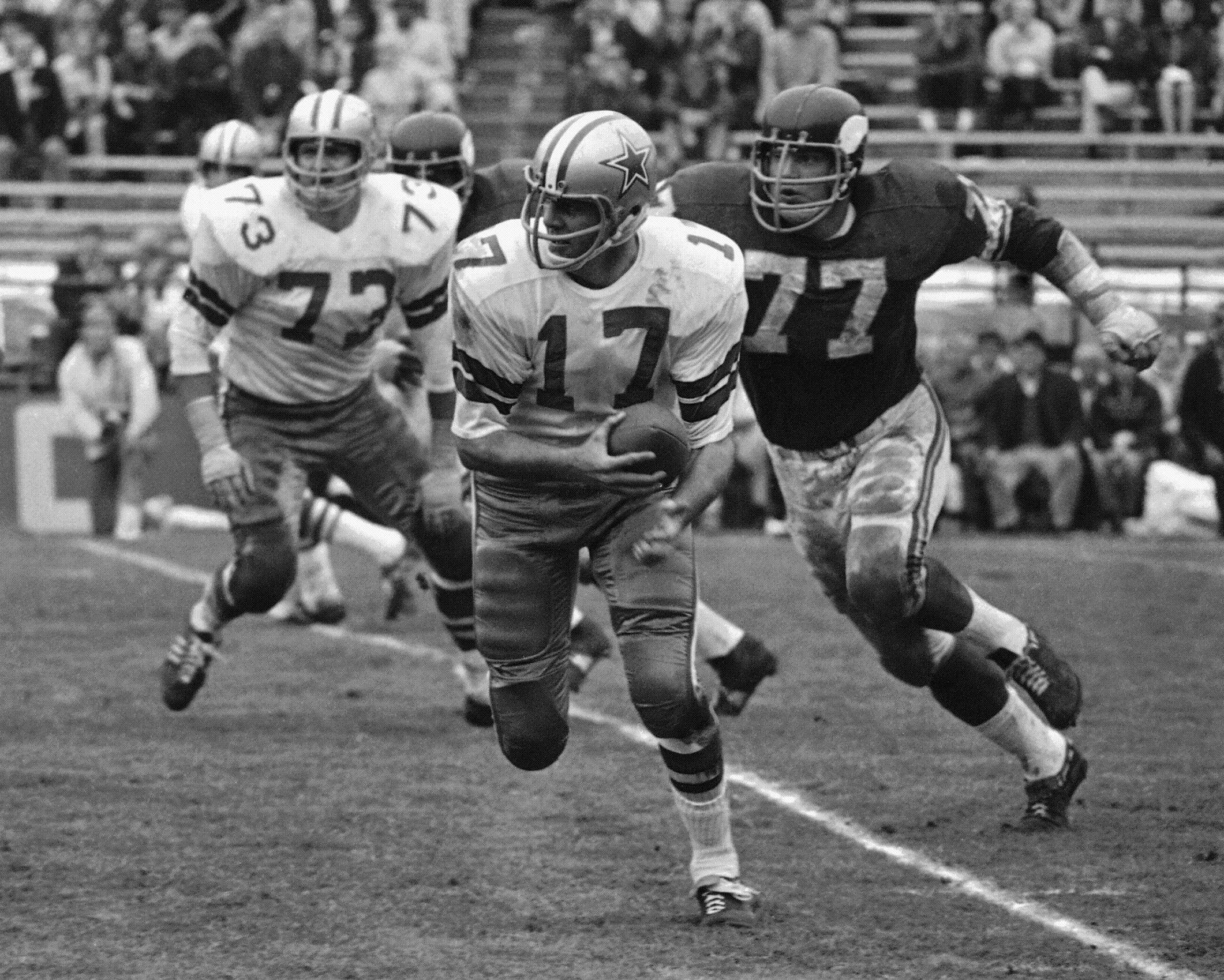 This Jan. 5, 1969, file photo shows Dallas Cowboys quarterback Don Meredith (17) running for 7-yards in the second quarter of an NFL playoff game, as Minnesota Vikings defensive tackle Gary Larsen (77) prepares to make the tackle, in Miami.