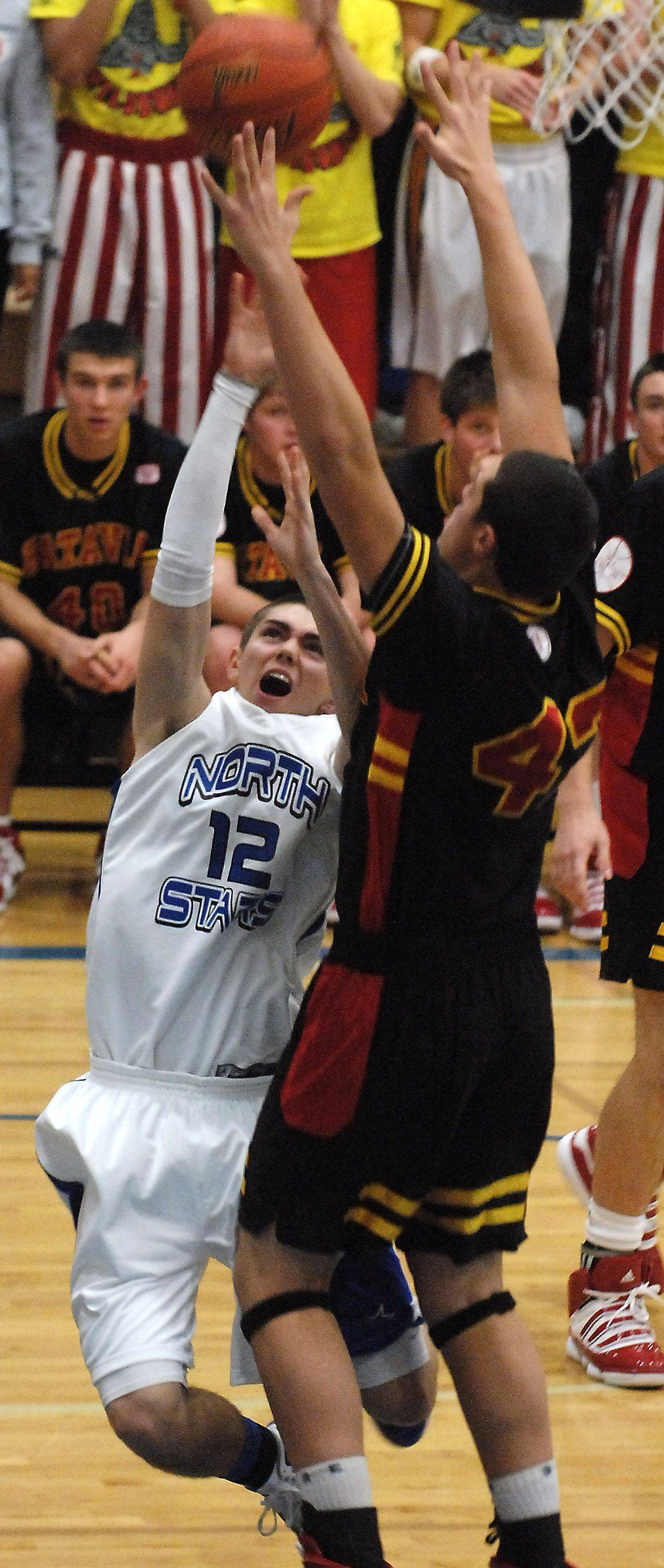 St. Charles North's Quinten Payne scores and gets fouled by Batavia's Cole Gardner during the opening minutes of Thursday's game in St. Charles.