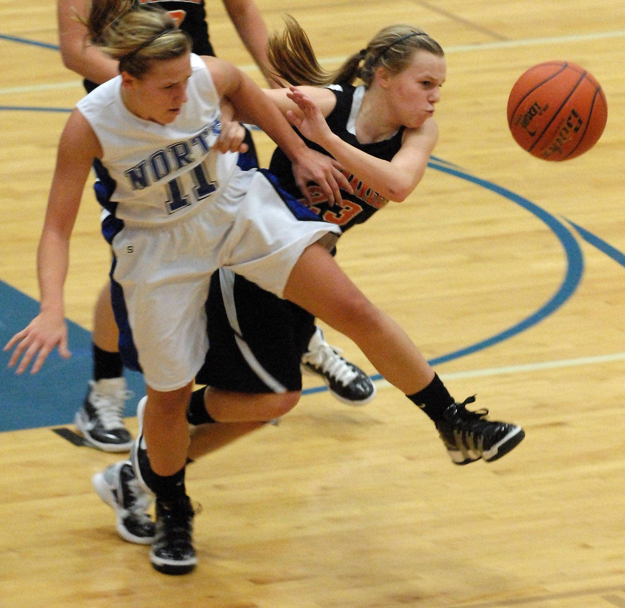 St. Charles North's Megan Booe and St. Charles East's Amanda Hilton scramble for a loose ball during Friday's game at St. Charles North.