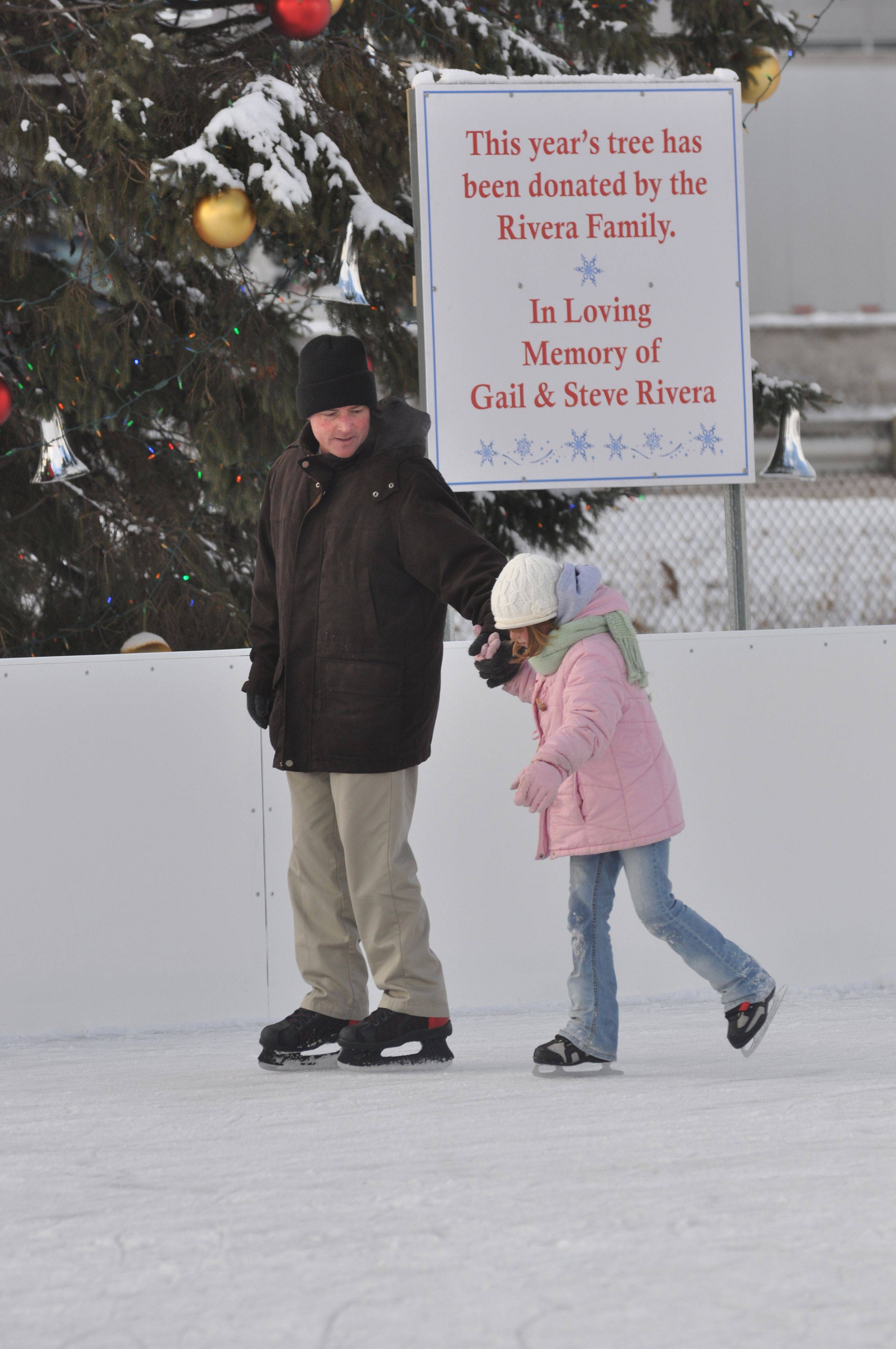 Sydney Cesare, 7, and her father Michael stop by the new outdoor skating rink in Rosemont during their stay at Embassy Suites.