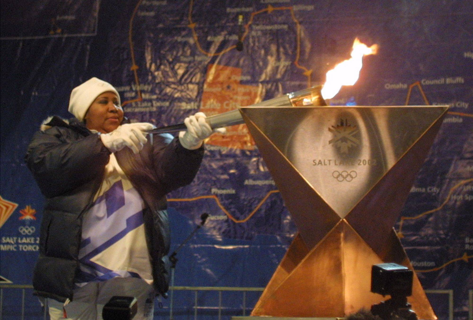 Singer Aretha Franklin lights a cauldron with the Olympic torch after completing her leg of the torch relay Sunday, Jan. 6, 2002, in Detroit.