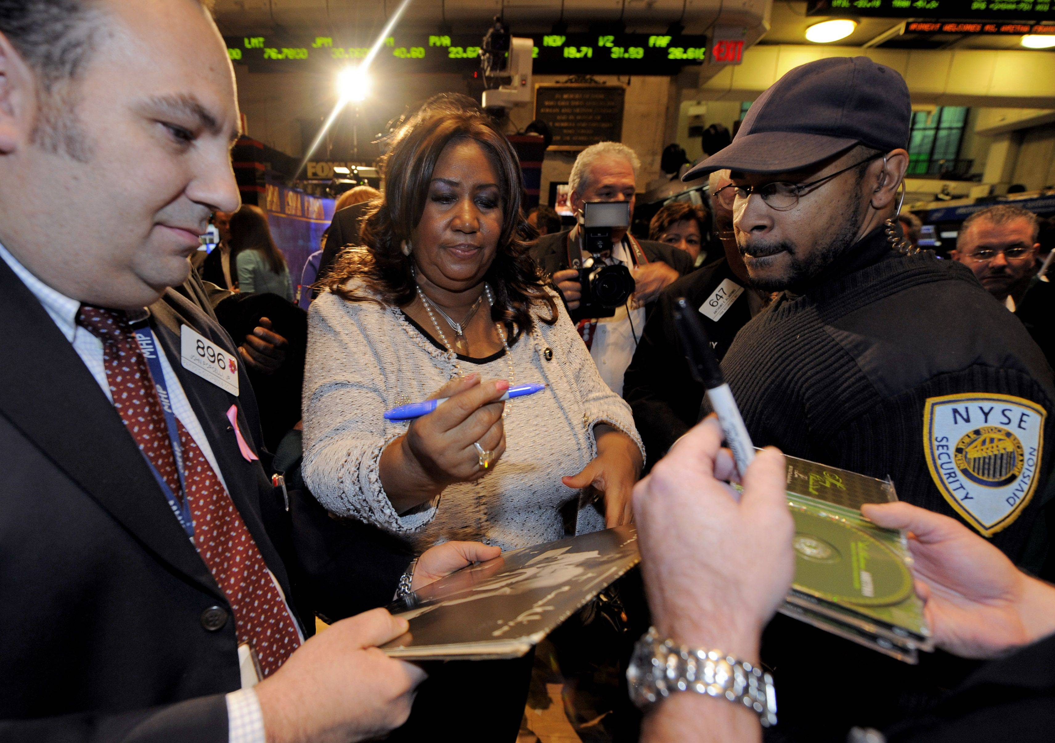 Singer Aretha Franklin signs autographs for traders on the floor of the New York Stock Exchange before she rings the closing bell, Thursday Dec. 4, 2008.