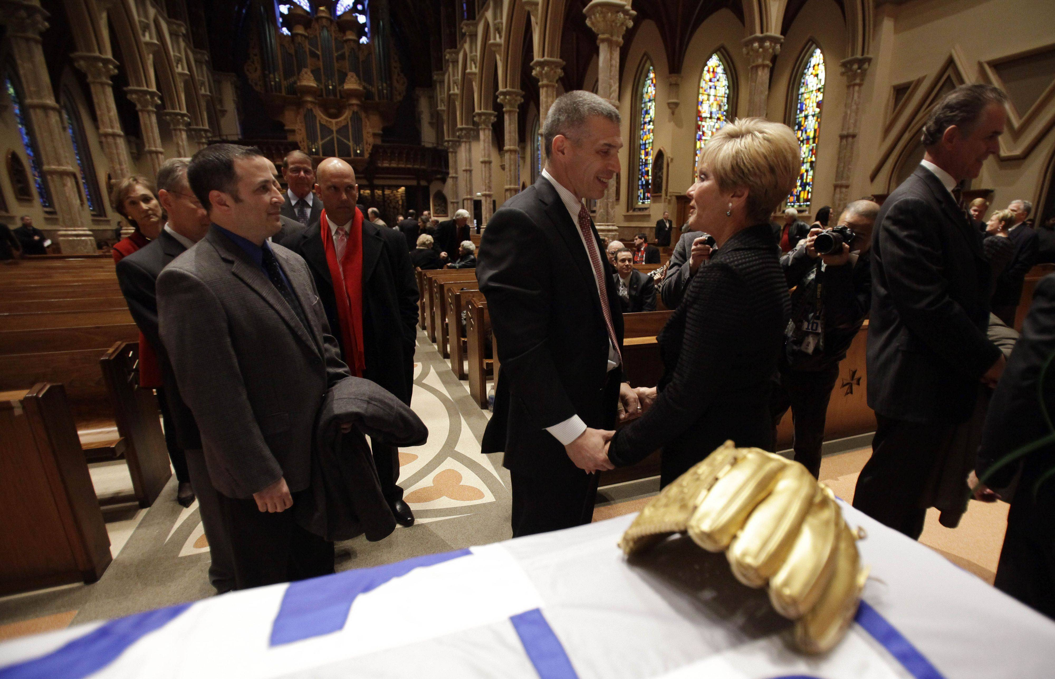 New York Yankees manager Joe Girardi, center left, talks to Vicki Santo, wife of Chicago Cubs great and longtime radio announcer Ron Santo, during the visitation at Holy Name Cathedral, Thursday, Dec. 9, 2010, in Chicago. Ron Santo, a nine-time all-star, died Thursday, Dec. 2 in an Arizona hospital from complication of bladder cancer. He was 70. (AP Photo/Nam Y. Huh, Pool)