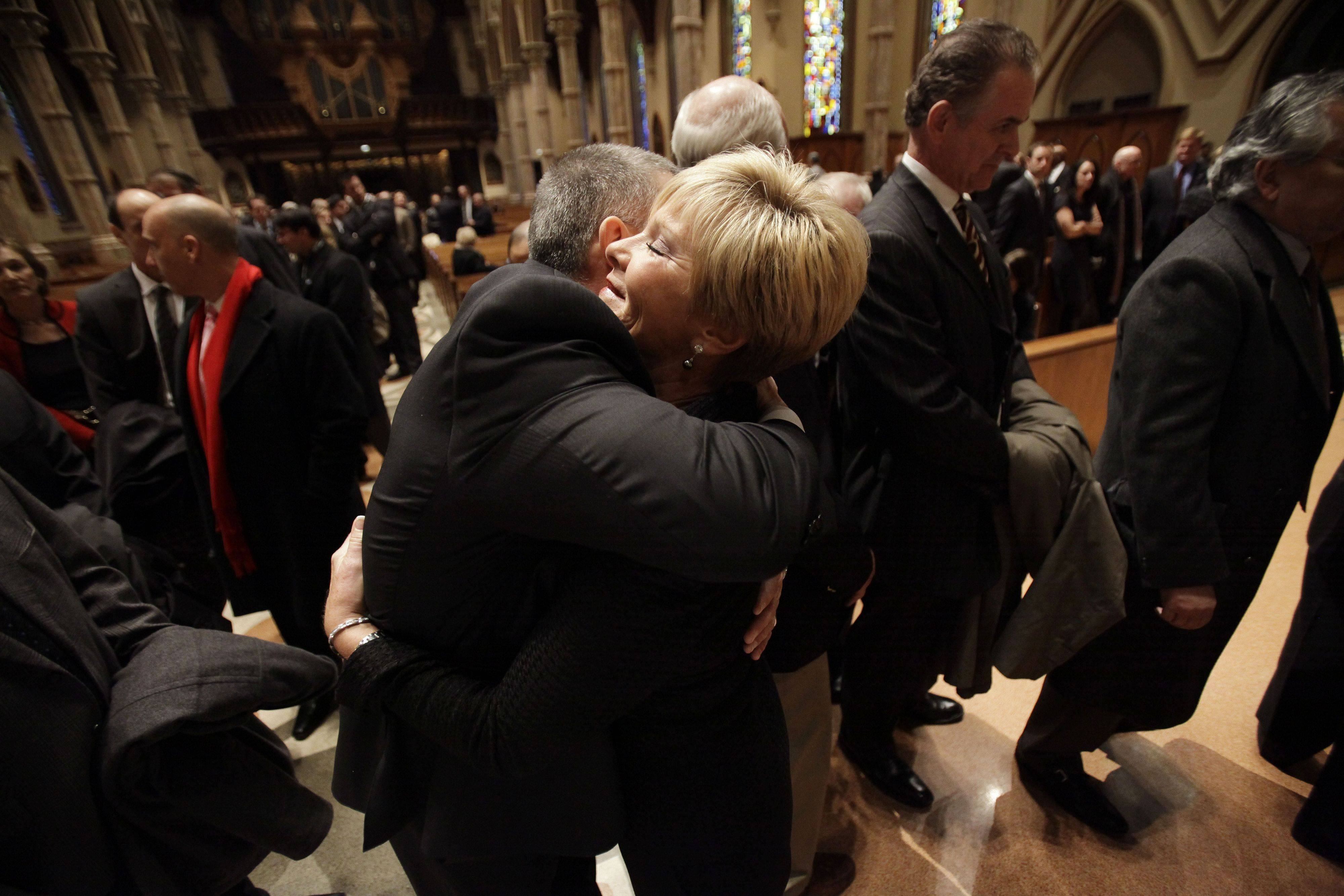 Vicki Santo, right, wife of Chicago Cubs great and longtime radio announcer Ron Santo, receives a hug from New York Yankees manager Joe Girardi during the visitation at Holy Name Cathedral, Thursday, Dec. 9, 2010, in Chicago. Ron Santo, a nine-time all-star, died Thursday, Dec. 2 in an Arizona hospital from complication of bladder cancer. He was 70. (AP Photo/Nam Y. Huh, Pool)