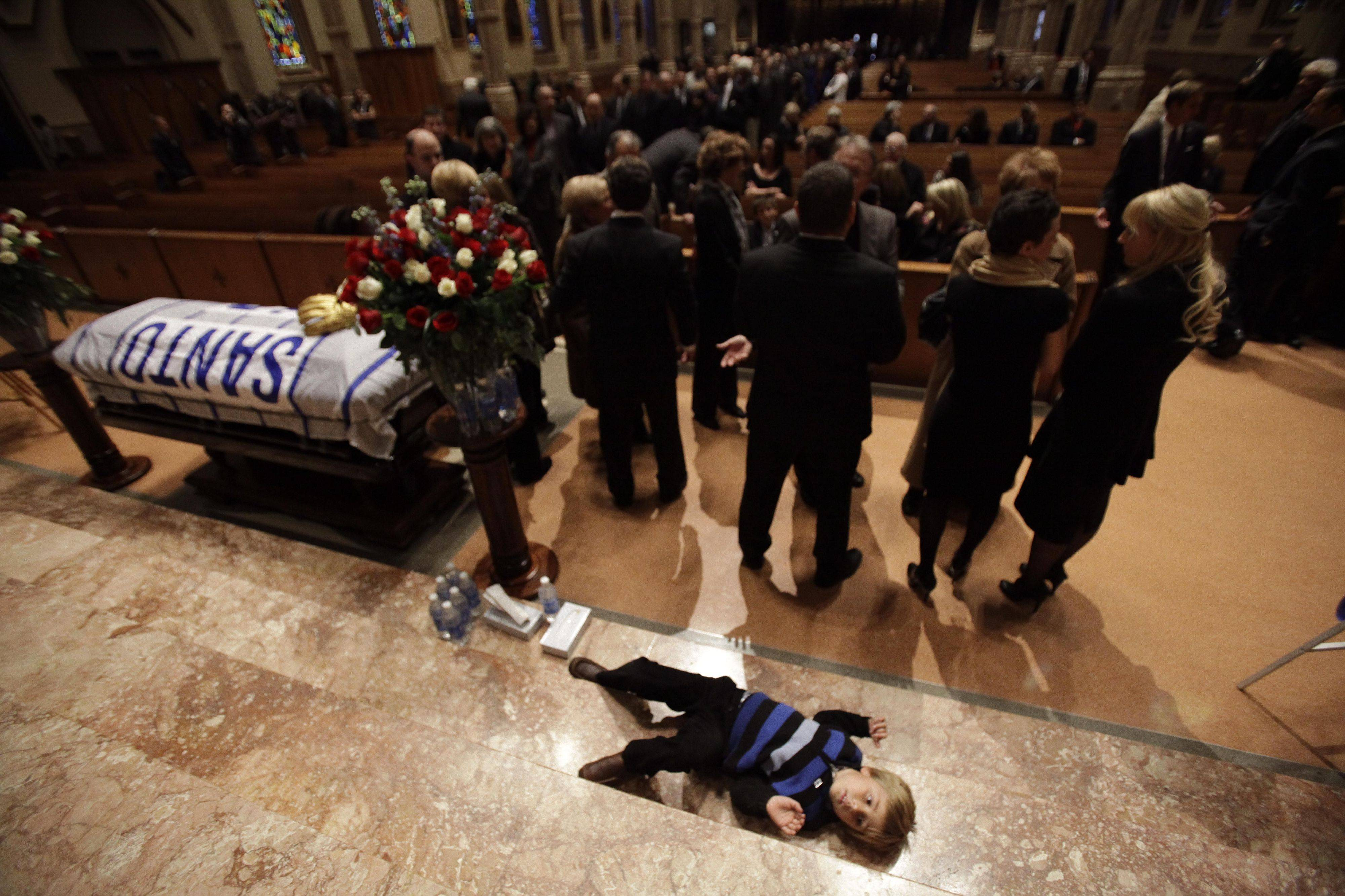 Spencer Brown, grandson of Chicago Cubs great and longtime radio announcer Ron Santo, lays on the altar during visitation at Holy Name Cathedral, Thursday, Dec. 9, 2010, in Chicago. The nine-time all-star died Thursday, Dec. 2 in an Arizona hospital from complication of bladder cancer. He was 70. (AP Photo/Nam Y. Huh, Pool)