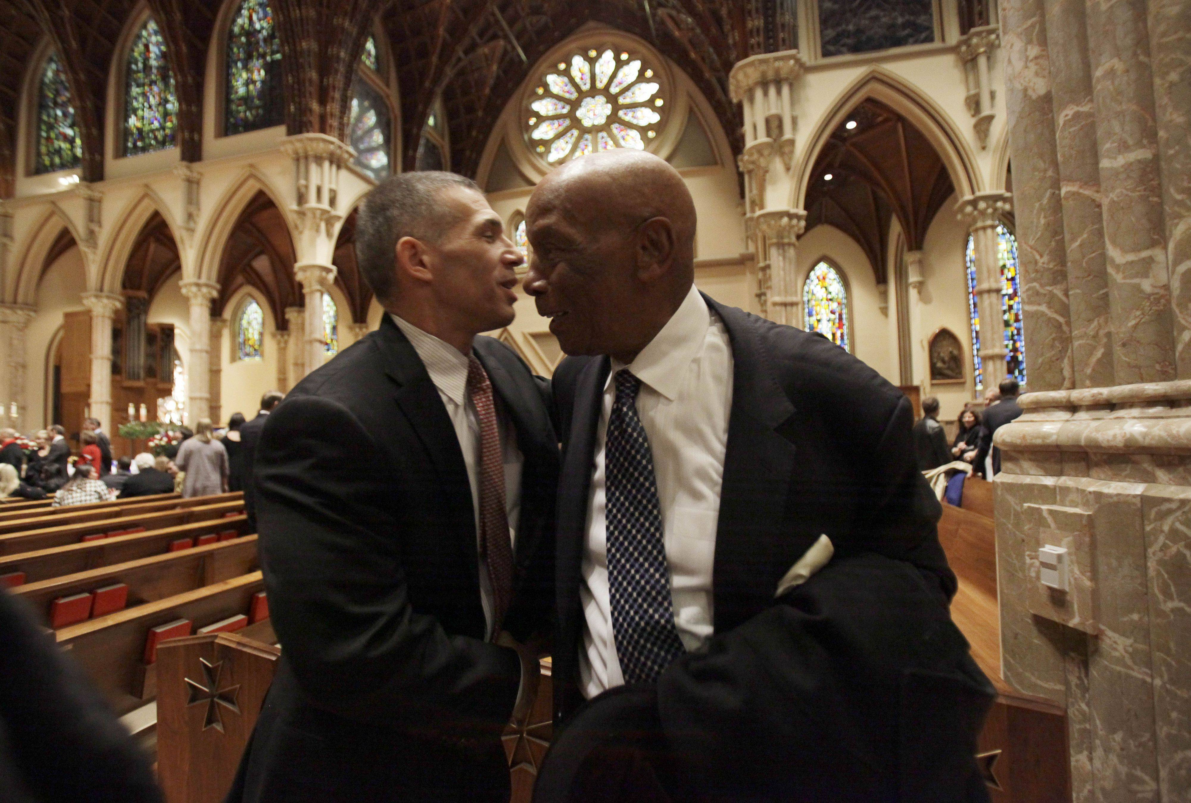 New York Yankees manager Joe Girardi, left, hugs Chicago Cubs great Ernie Banks during the visitation for Chicago Cubs great and longtime radio announcer Ron Santo at Holy Name Cathedral, Thursday, Dec. 9, 2010, in Chicago. Santo, a nine-time all-star, died Thursday, Dec. 2 in an Arizona hospital from complication of bladder cancer. He was 70. (AP Photo/Nam Y. Huh, Pool)