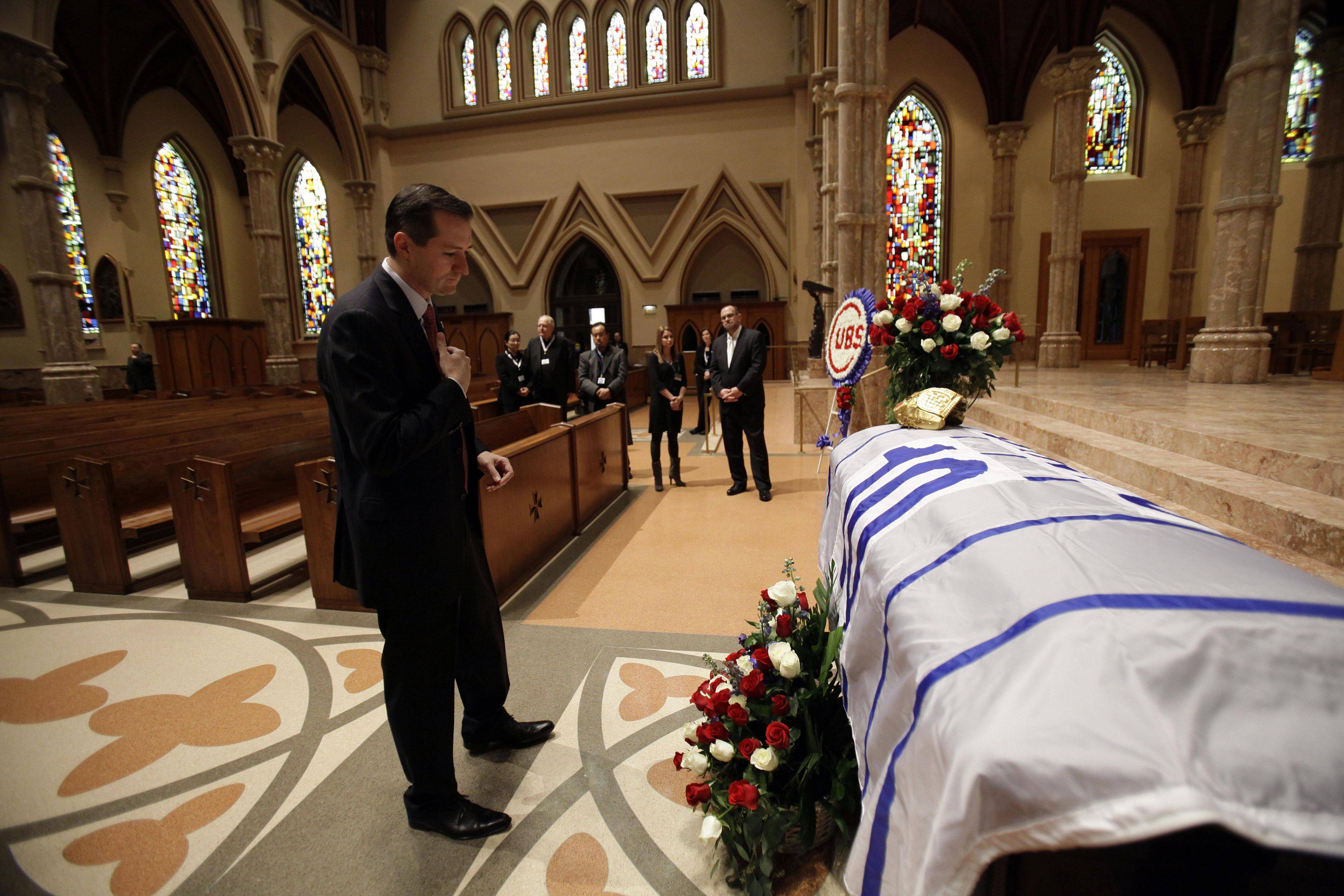 Chicago Cubs chairman Tom Ricketts prays as the casket for Chicago Cubs great and longtime radio announcer Ron Santo arrives during the visitation at Holy Name Cathedral, Thursday, Dec. 9, 2010, in Chicago. The nine-time all-star died Thursday, Dec. 2 in an Arizona hospital from complication of bladder cancer. He was 70. (AP Photo/Nam Y. Huh, Pool)
