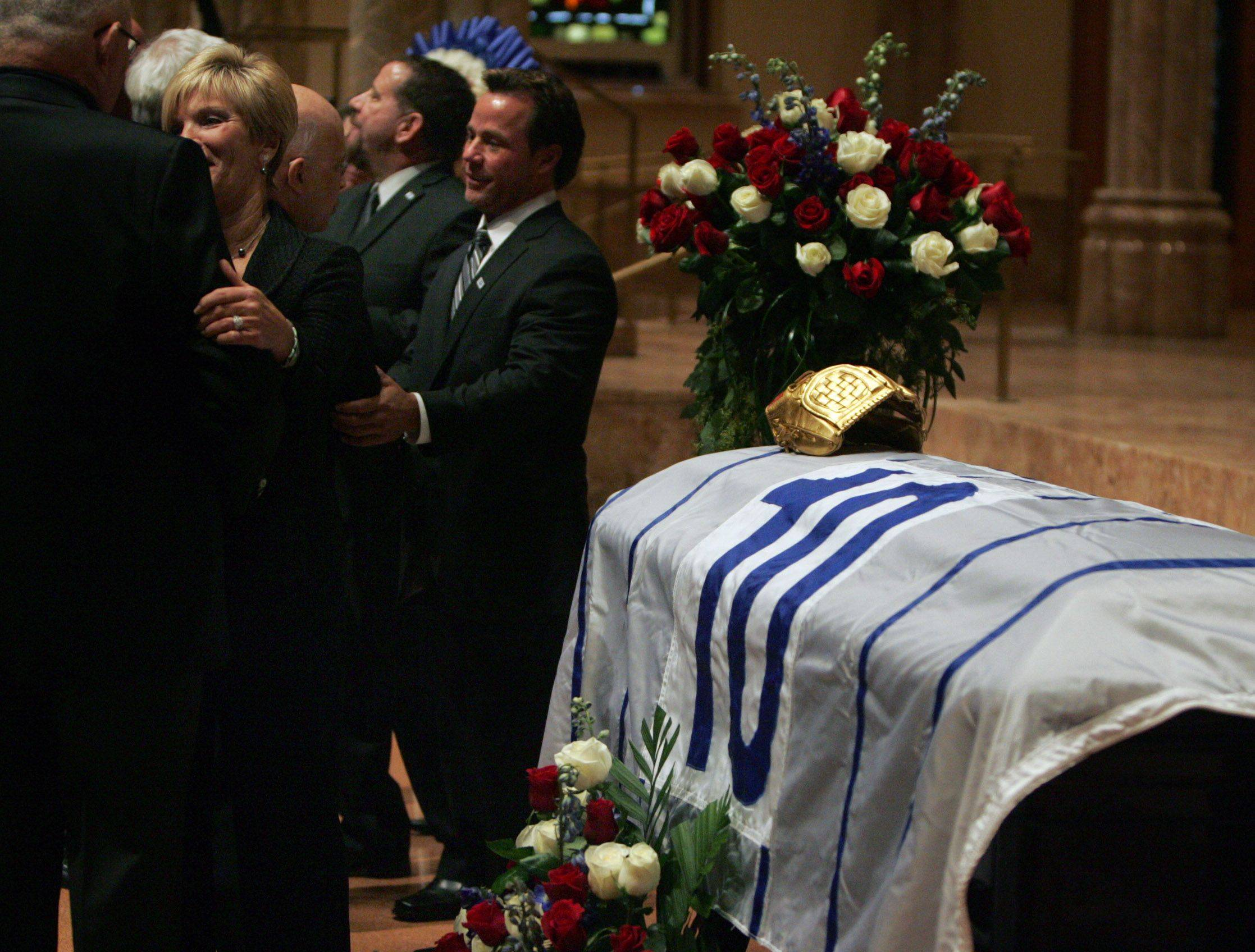 Ron Santo's son Ron Jr. and wife Vicki Santo stand next to the casket draped with the flag that flew over Wrigley Field when his number 10 was retired as well as his gold glove at Holy Name Cathedral.