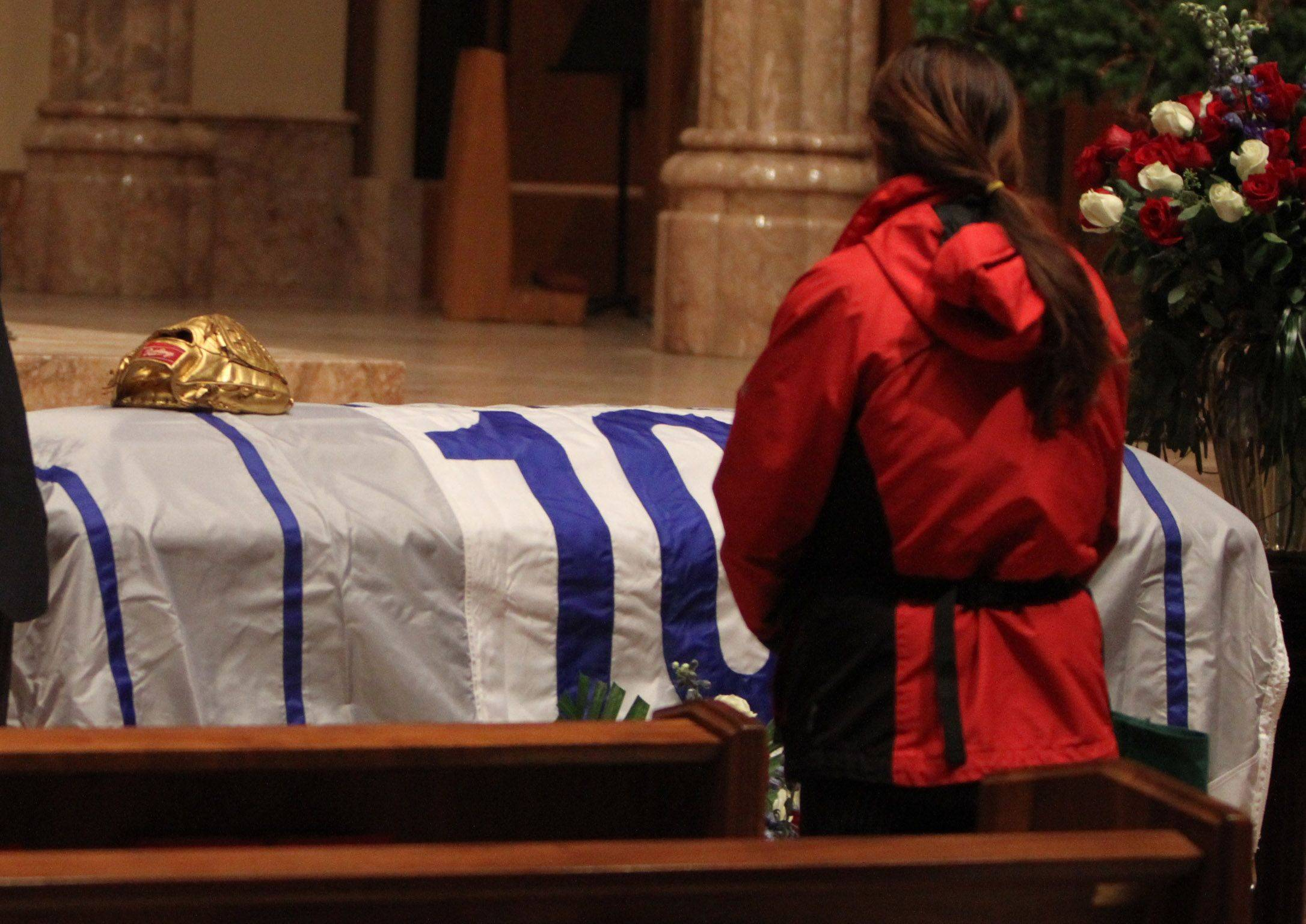 A Chicago Cubs fan looks down at Ron Santo's casket with Cubs employee John Oboikowitch, left.