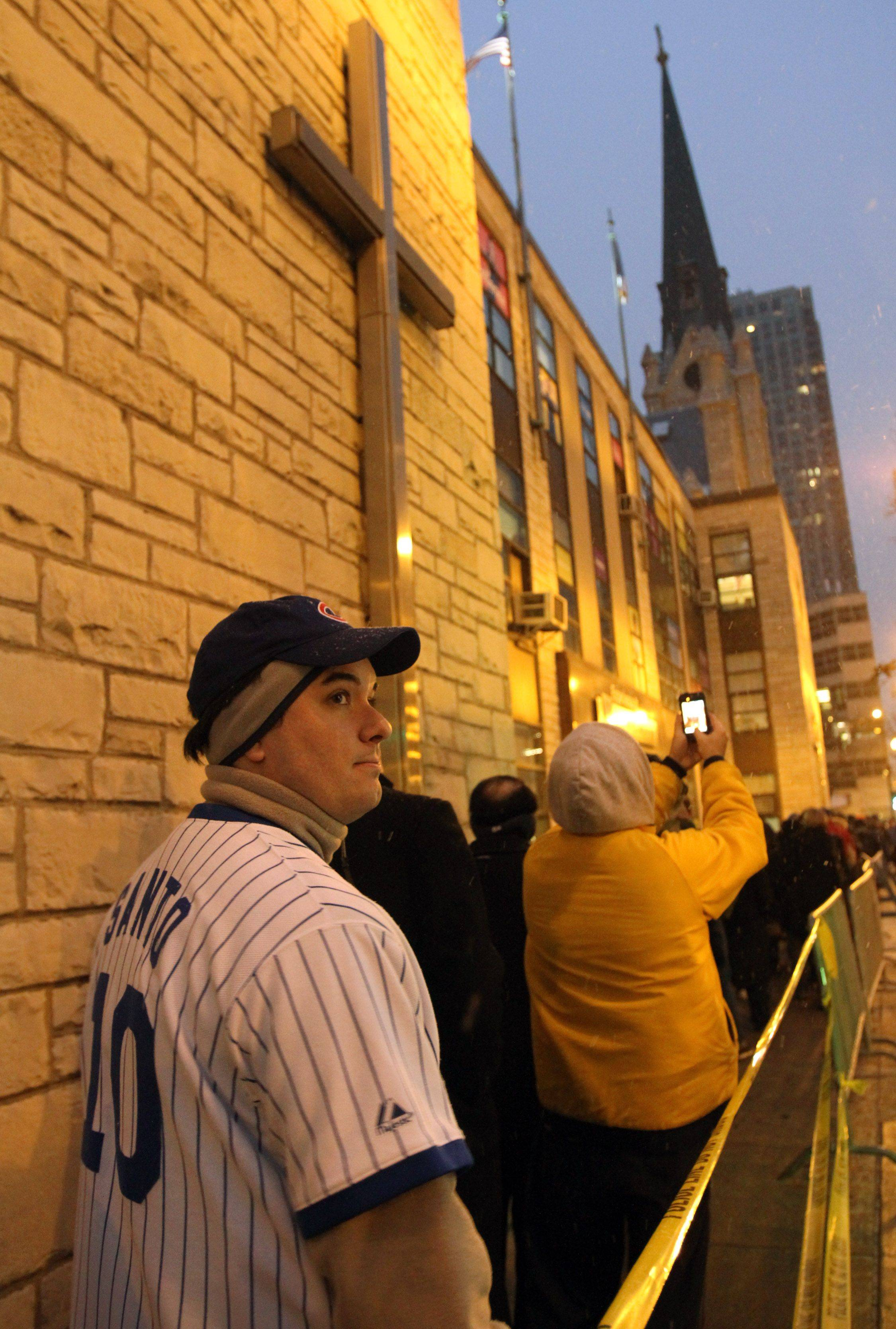 Chicago Cubs fan Dan Maratto of Chicago, wearing a number 10 jersey, waits in line on State Street for the public visitation for Chicago Cubs legend Ron Santo.