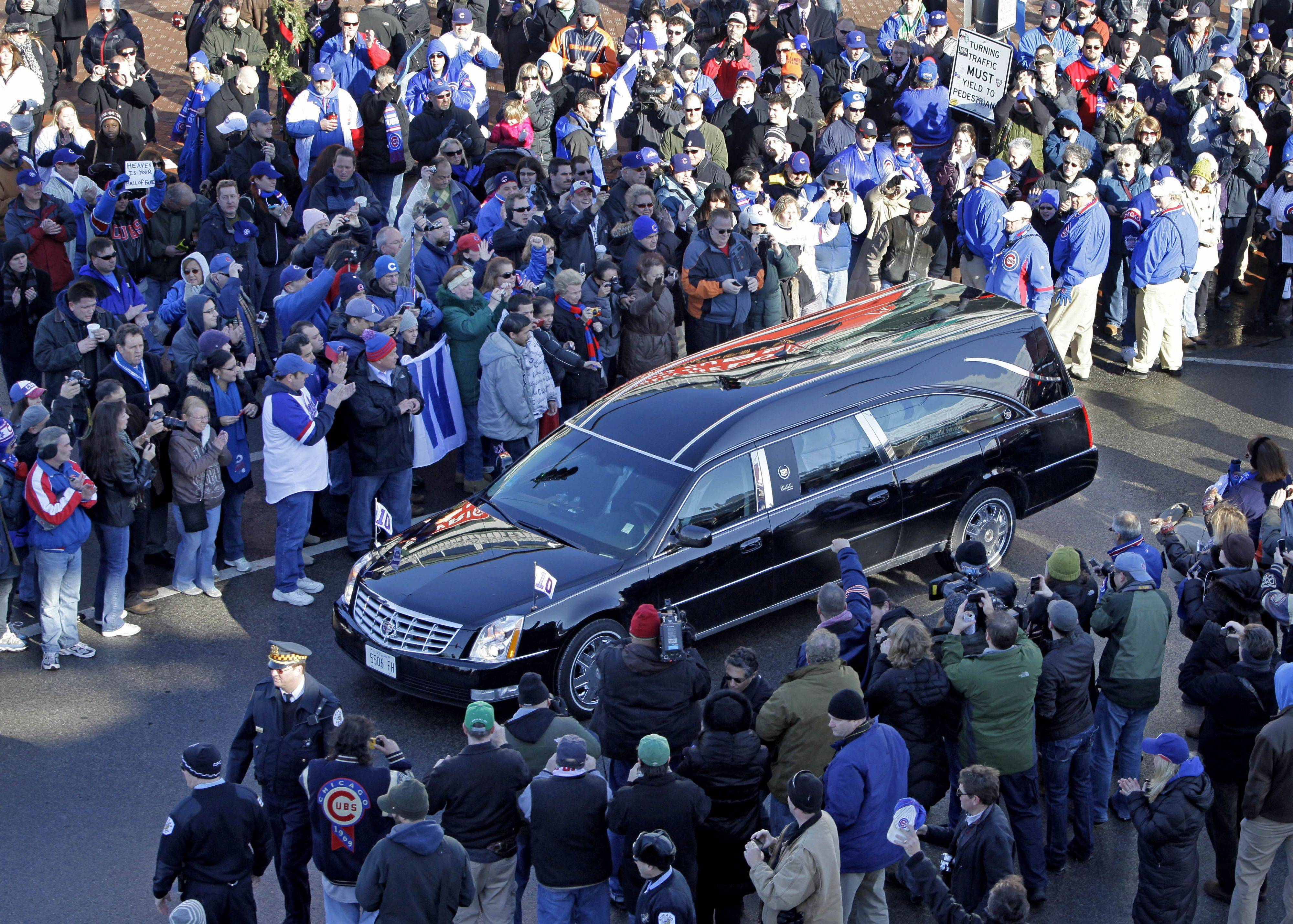 Baseball fans pay their respect as the funeral procession for Ron Santo drives past Wrigley Field.