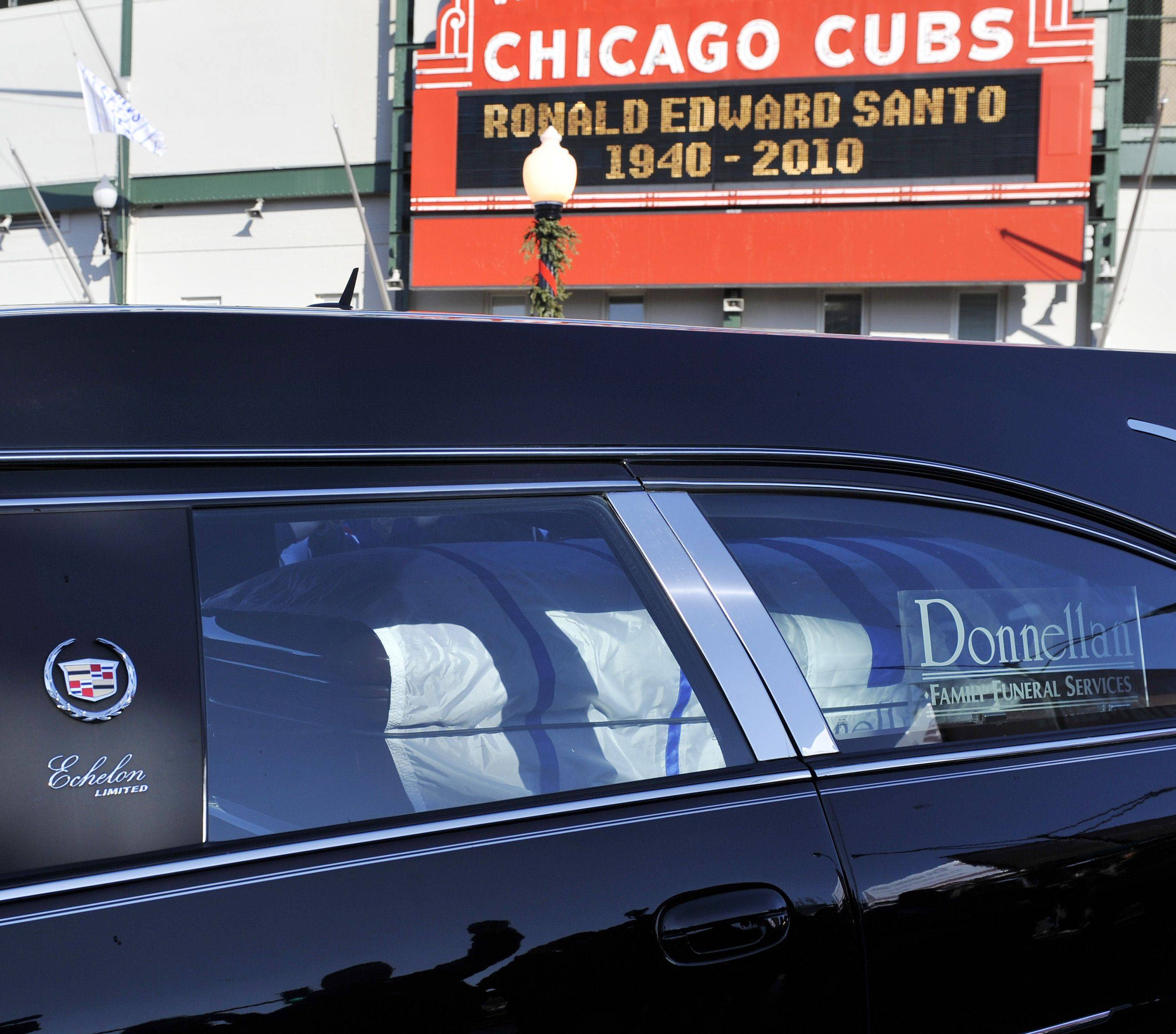 The funeral procession for former Chicago Cubs great Ron Santo drives past Wrigley Field.