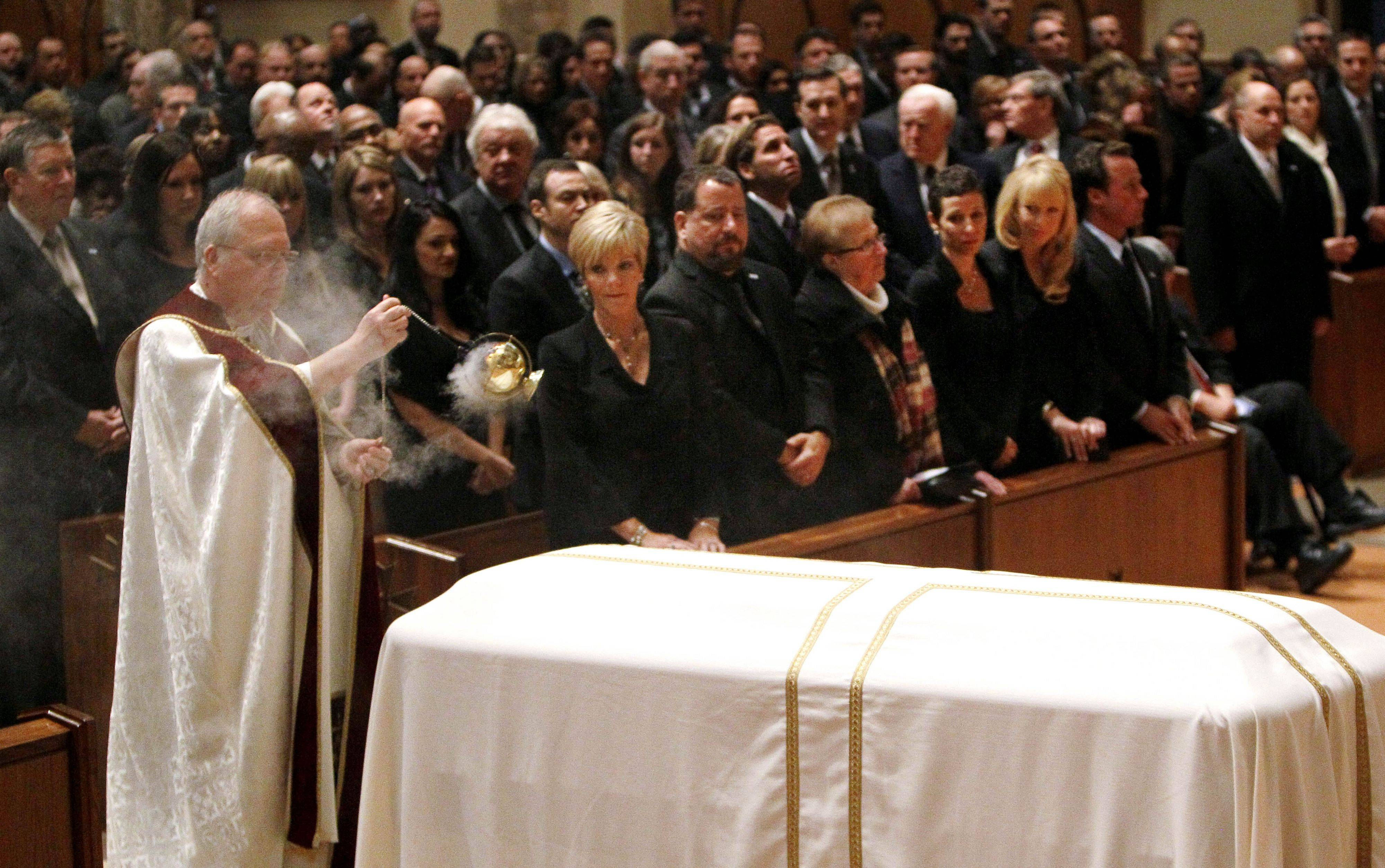 Monsignor Daniel G. Mayall blesses Chicago Cubs' great Ron Santo's casket as Santo's family looks on during the funeral services.
