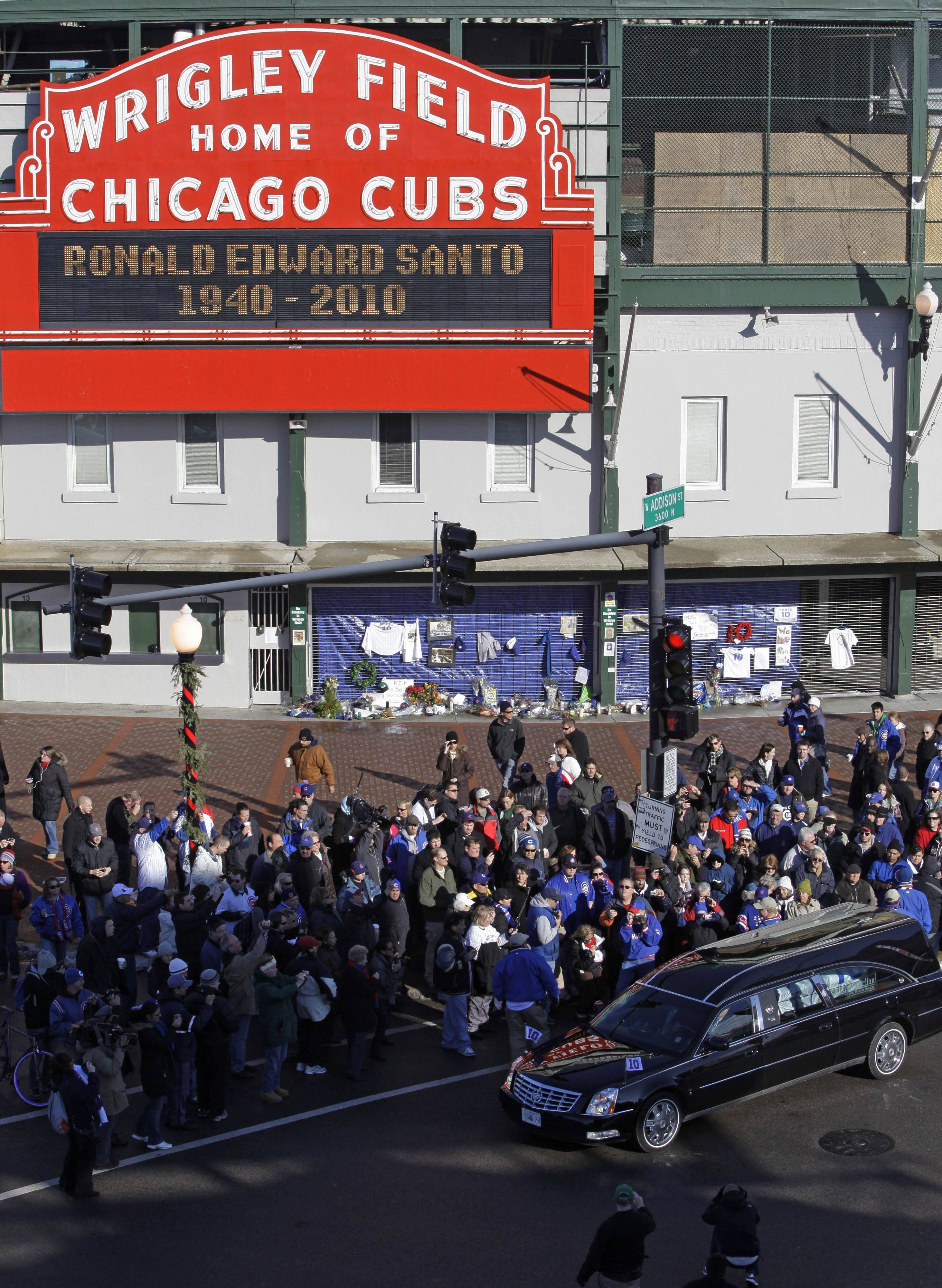 The funeral procession for former Chicago Cubs great and longtime radio announcer Ron Santo drives past Wrigley Field on Friday.