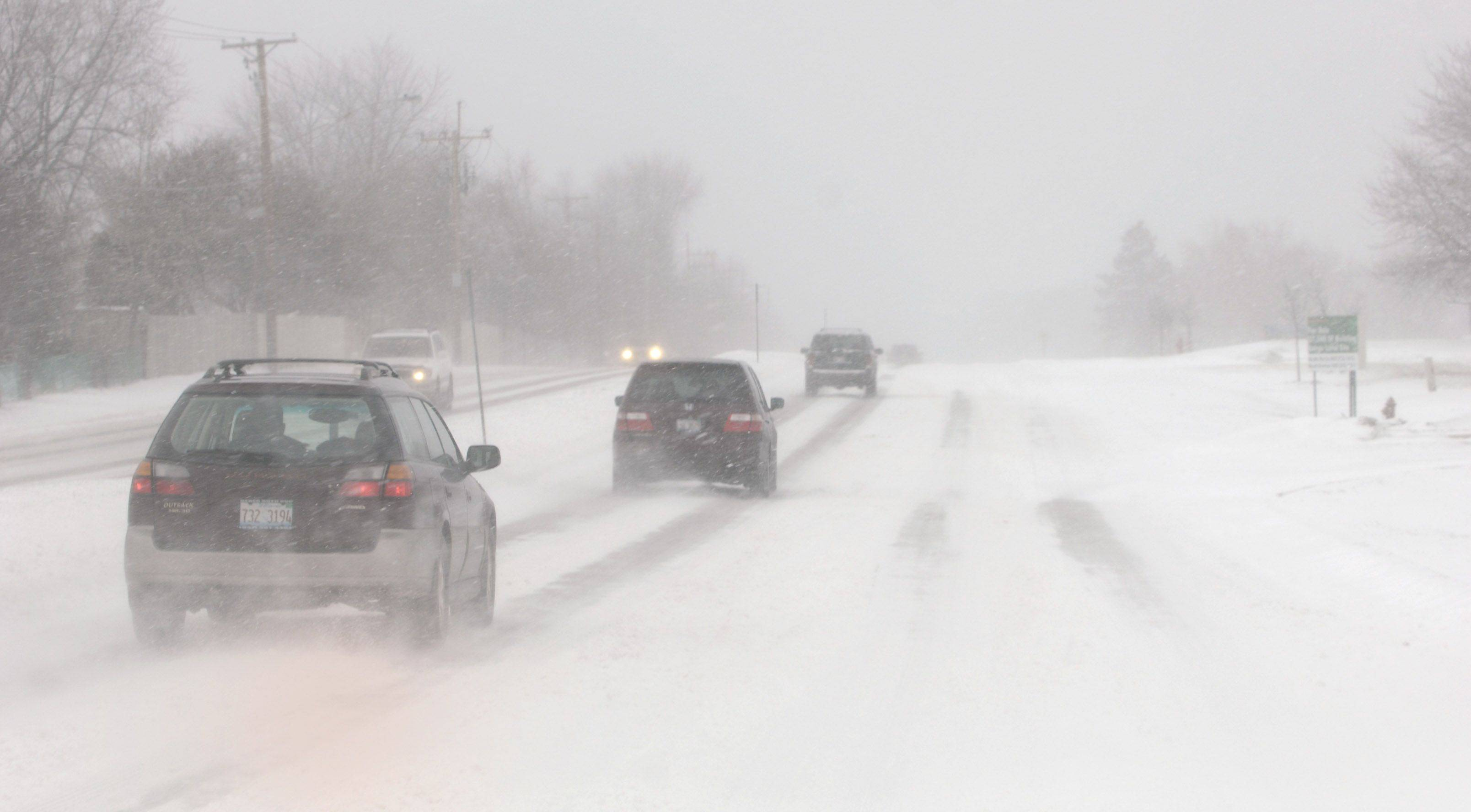 The blowing snow nearly erases the lanes along Route 22 in Lake County.