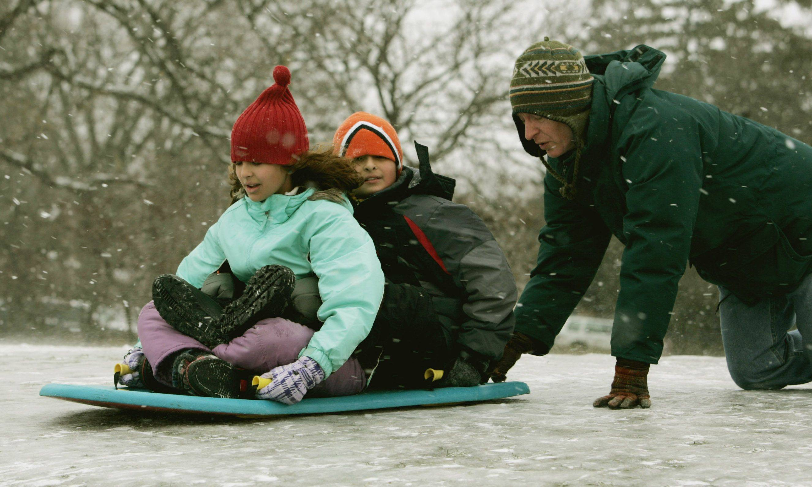 Jerry Novick, of Naperville gives his children Kara, 11, and Matt, 9, a push as they sled down a hill Sunday at Rotary Hill in Naperville.