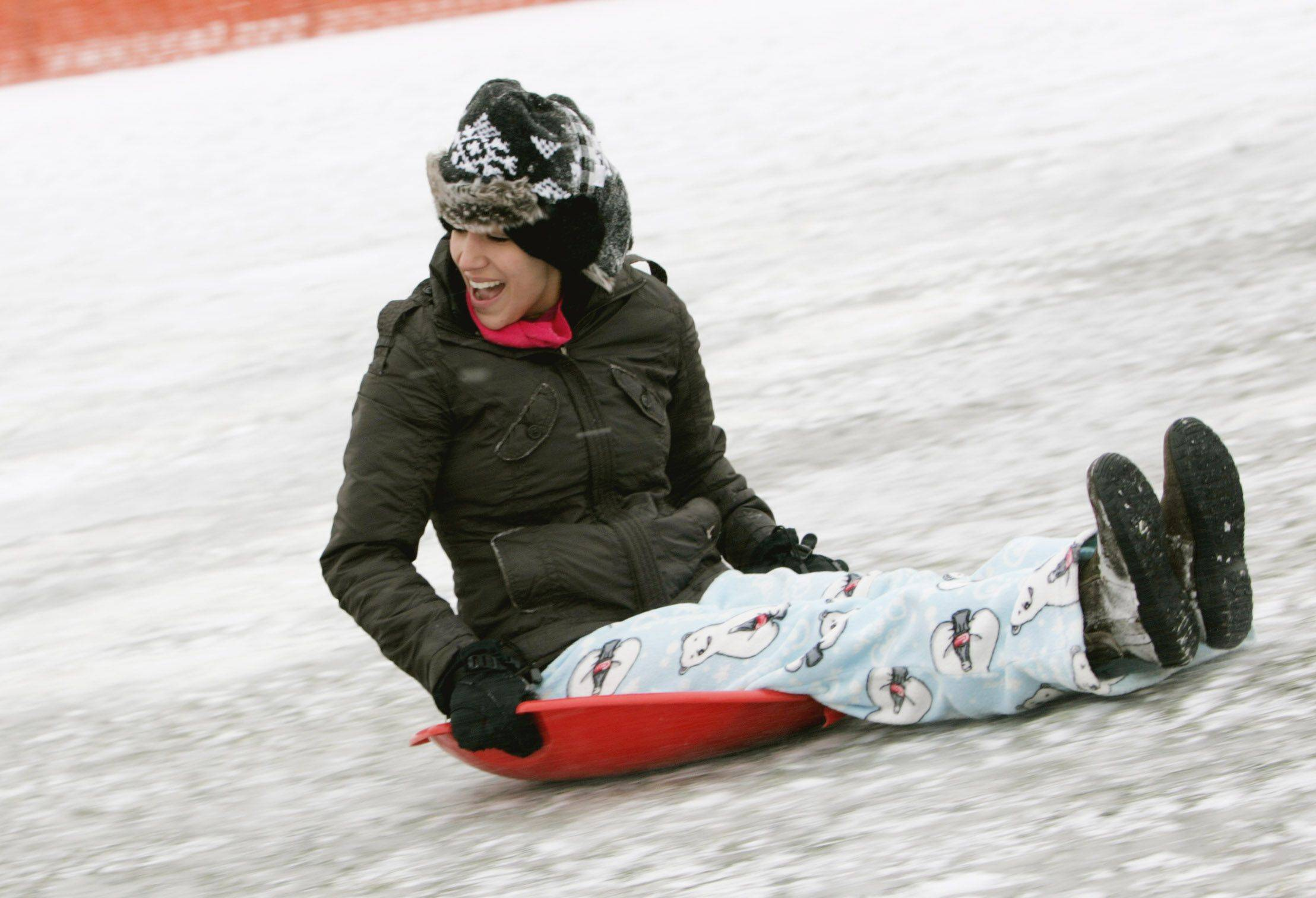 Kerry Novick, who is in town from Florida to visit her family in Naperville, sleds down a hill at Rotary Hill in Naperville.