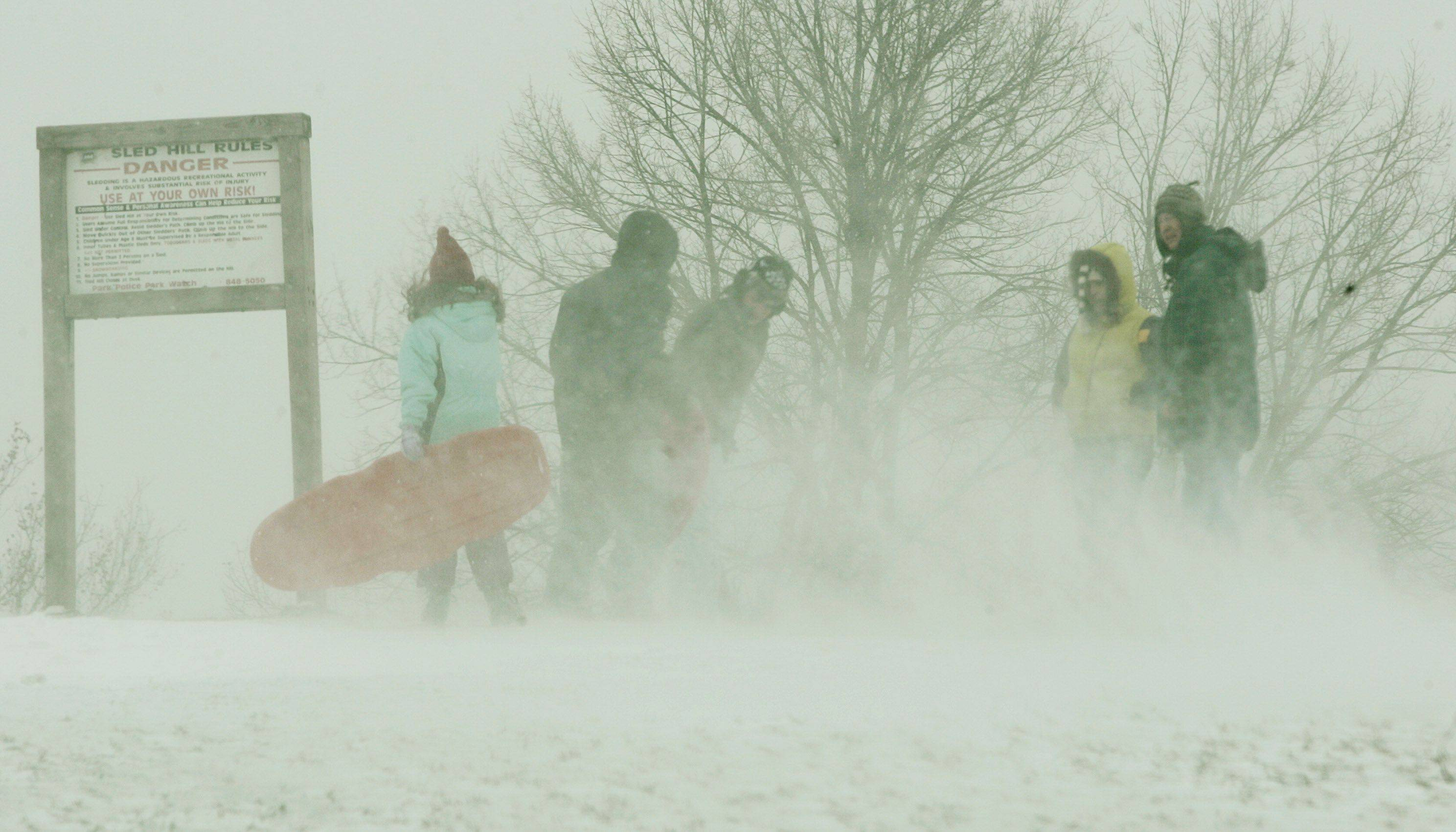 Naperville residents fight cold and wind as they sled down a hill Sunday in Naperville.