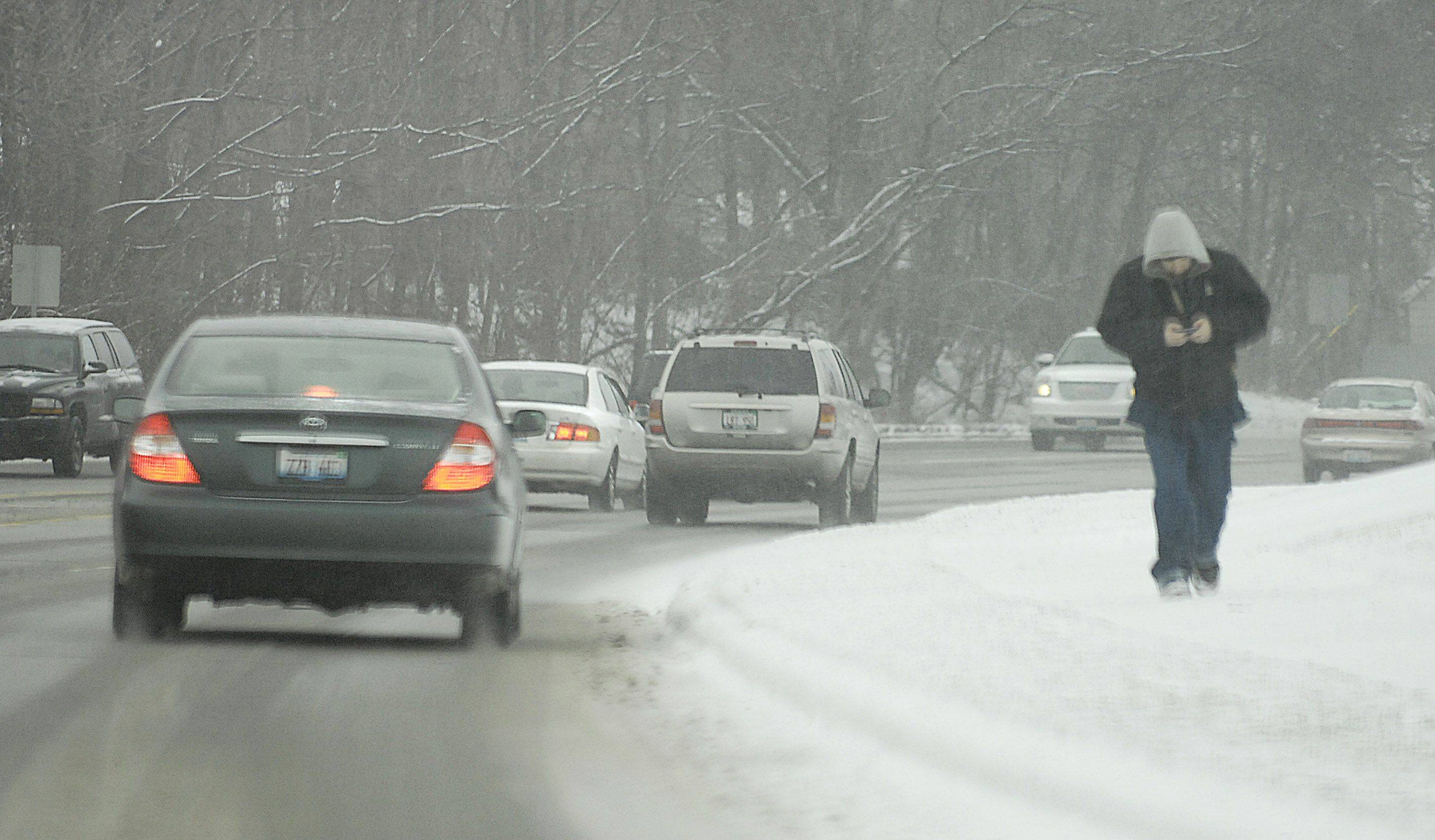 A man keeps his head down as he makes his way up a hill on Algonquin Road in Algonquin Sunday afternoon.