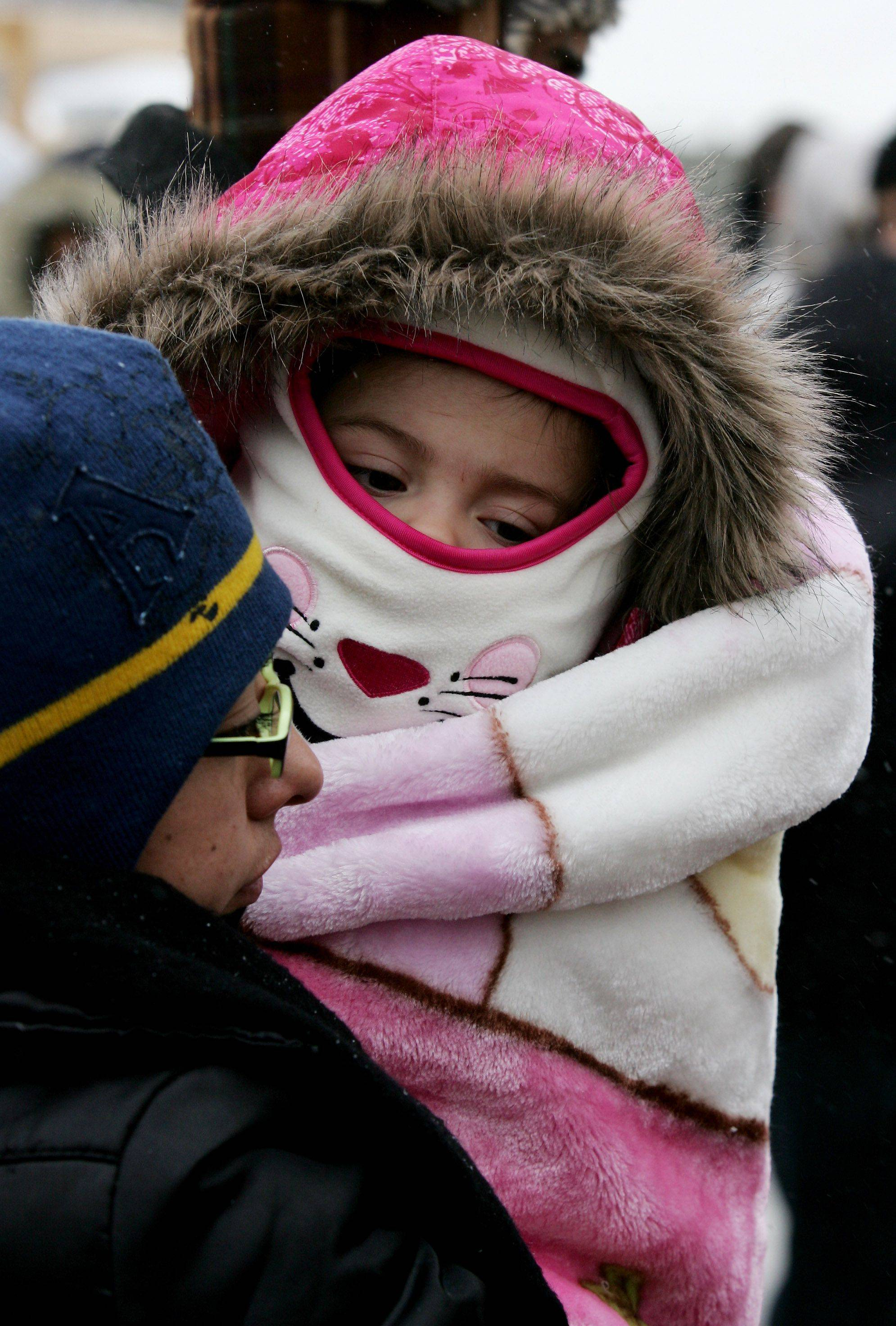 Ariadna Galvan of West Chicago holds her daughter Neftaly, 15-months-old, who is bundled up for the cold during the second day of the Shrine of Our Lady of Guadalupe event Sunday at Maryville Academy in Des Plaines.