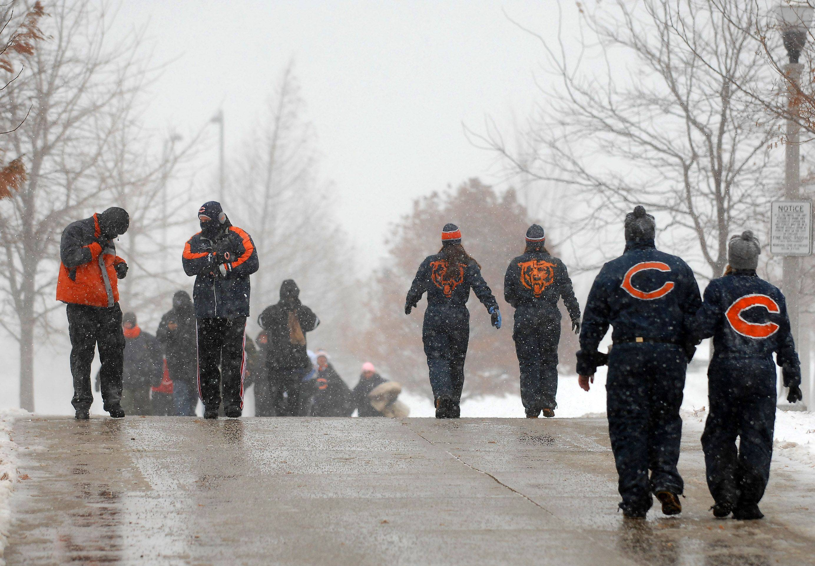 Fans walk through blowing snow to get to the stadium before Sunday's game at Soldier Field in Chicago.