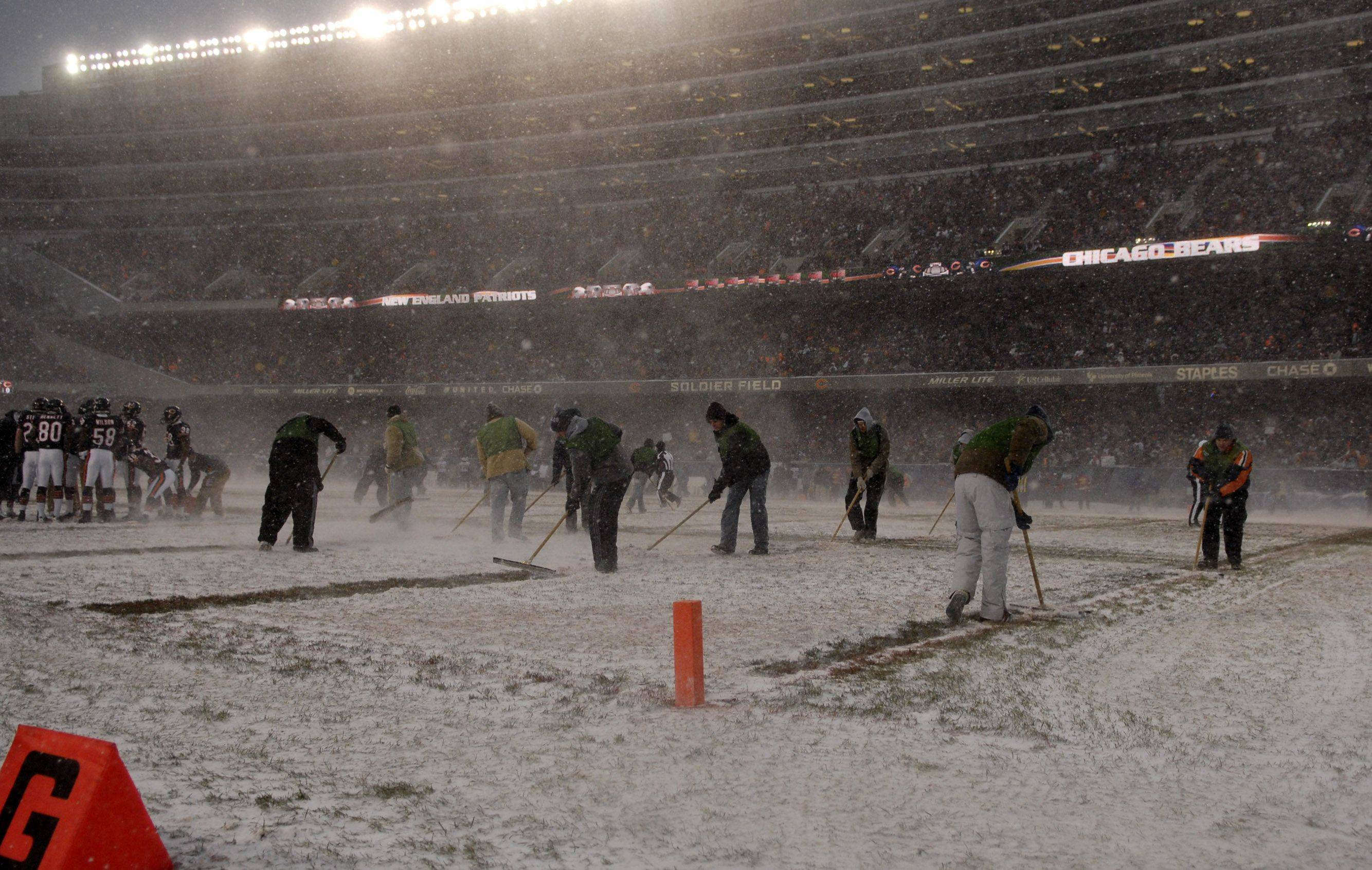 The grounds crew sweeps and squeegees the field during a timeout of Sunday's game at Soldier Field in Chicago.