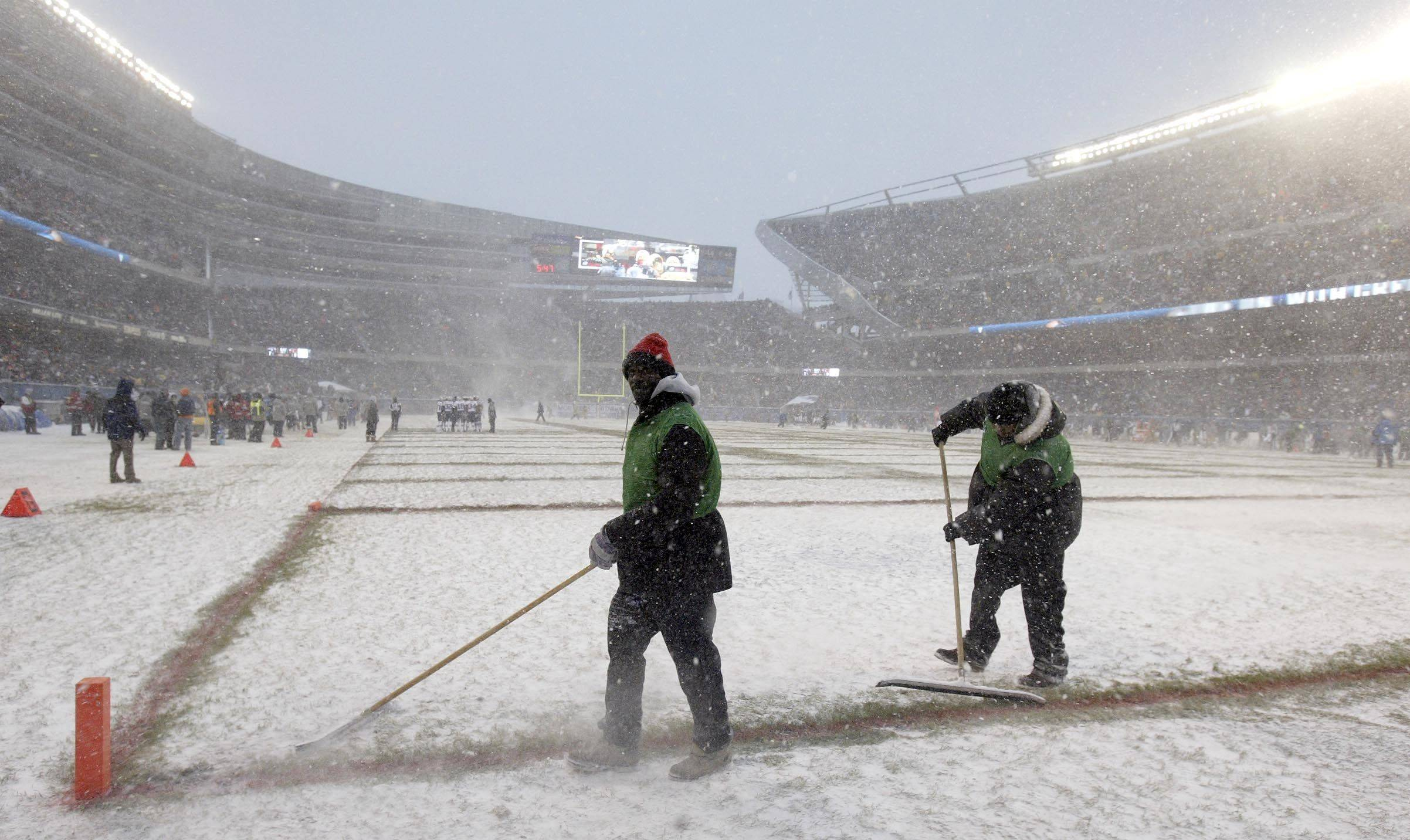Ground crews clear the field at Soldier Field in Chicago before the game between the Chicago Bears and the New England Patriots.