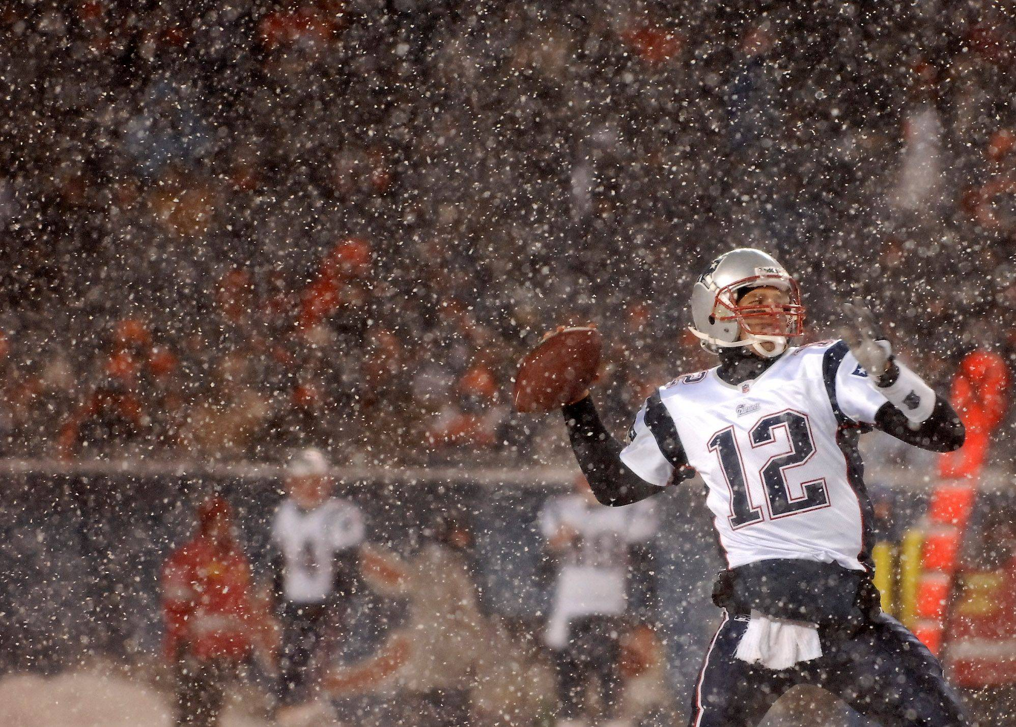 New England Patriots quarterback Tom Brady rears back to throw a long pass.