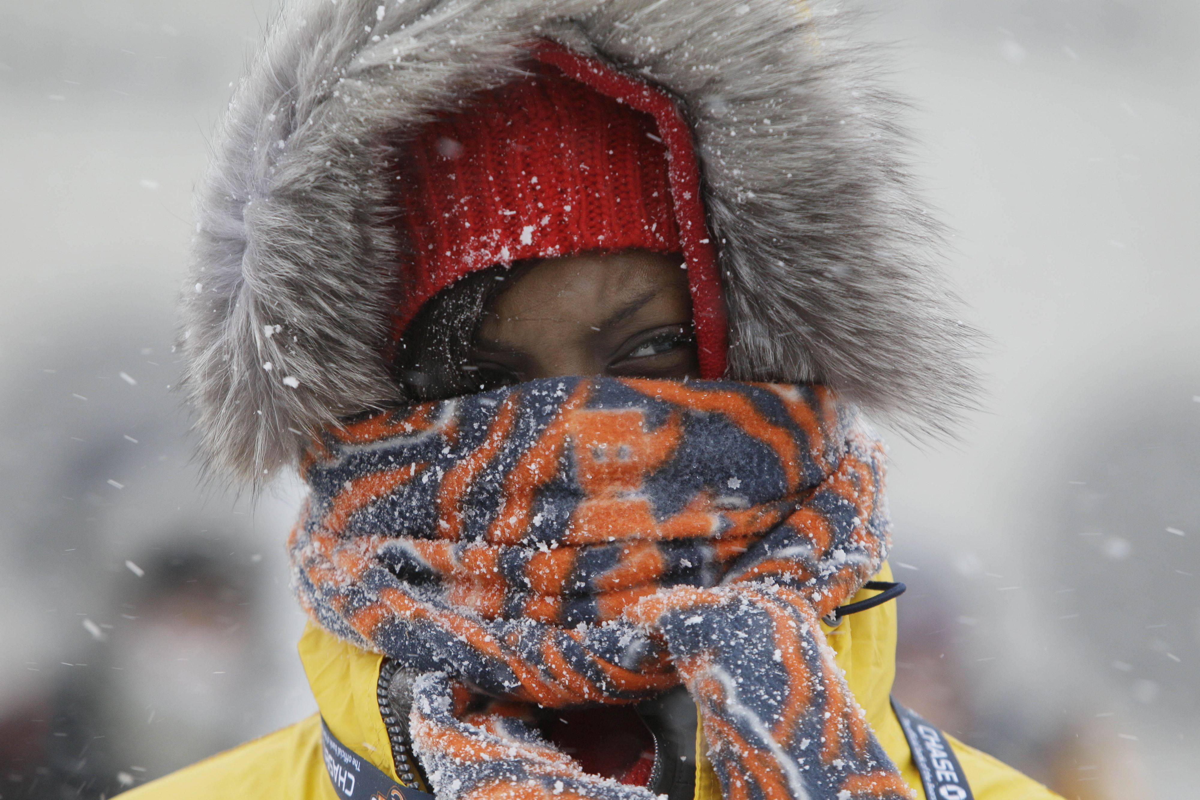 Chicago Bears fan Janise Ford arrives bundled up during a snowstorm at Soldier Field before an NFL football game between the Bears and the Patriots in Chicago.