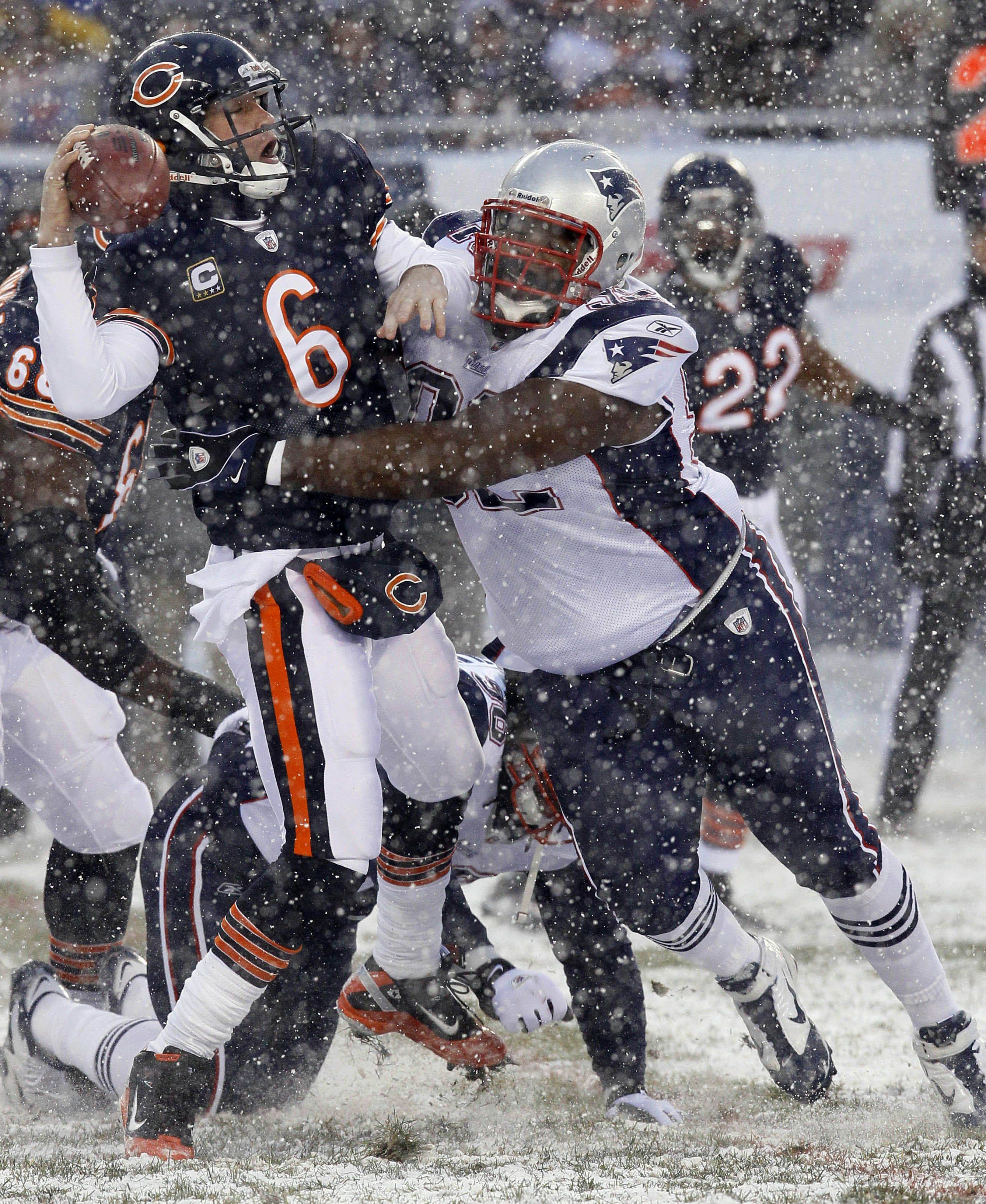 New England Patriots defensive tackle Gerard Warren, front right, and defensive end Jermaine Cunningham, bottom left, combine to sack Chicago Bears quarterback Jay Cutler in the first half.