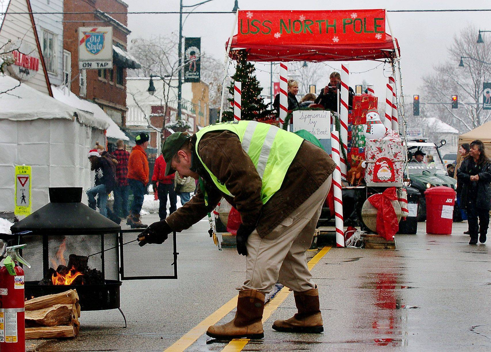 Lee Zimmerman of the Community Emergency Response Team stokes the flames of a fire pit during the Holiday Walk on Main Street in downtown Wauconda celebrating the Christmas season.