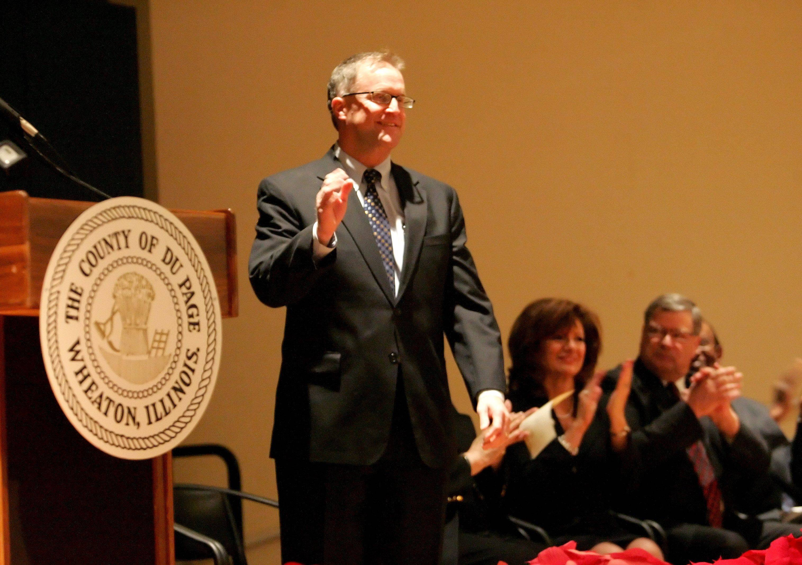Dan Cronin acknowledges the applause after he is sworn in as the new DuPage County Board Chairman in Wheaton on Monday.
