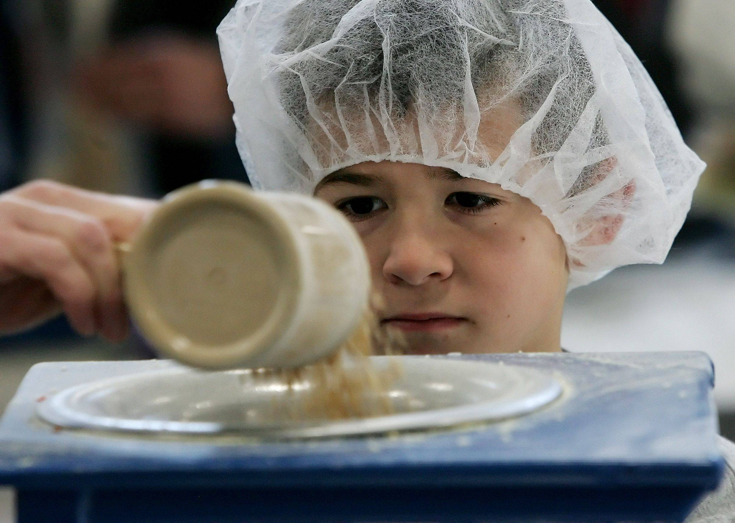 Aaron Ketchmark, 6, of Kouts, Indiana watches as rice is poured into a bag. Aaron was attending a birthday party for his cousin Cameron Tonkery of Hainesville who celebrated his eleventh birthday by having his party at the Feed My Starving Children event at the Lake County Fairgrounds. Party goers spent time packaging meals to be sent to starving children around the world.