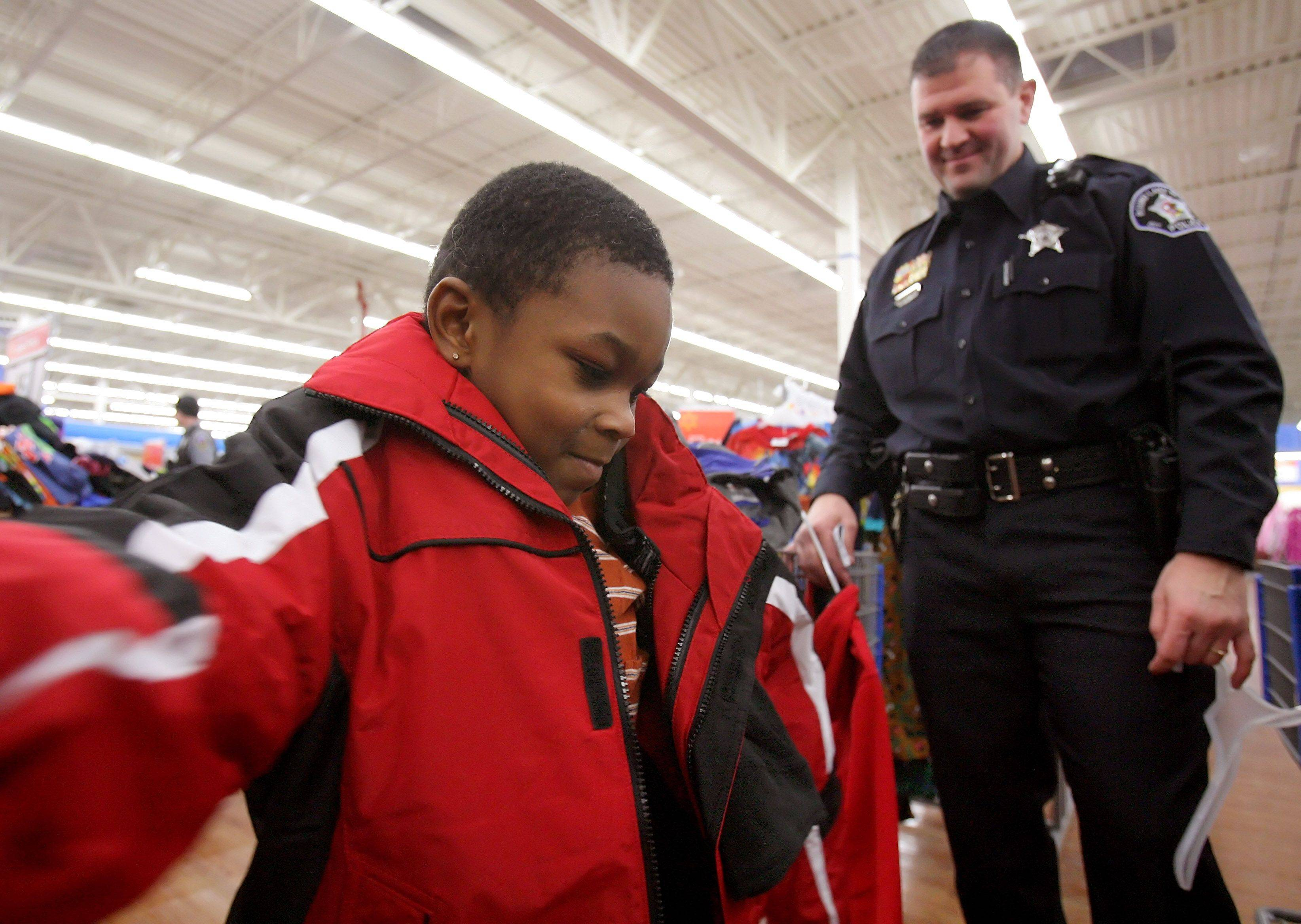 Round Lake Beach police officer Steve Sandacz watches as five-year-old Anthony Branch of Round Lake Beach tries on a winter coat as needy children were met by police officers and escorted through the Wal-Mart store to shop for Christmas presents Monday. This year because of generous donations, the Village of Round Lake Beach had 60 kids participate in the program.