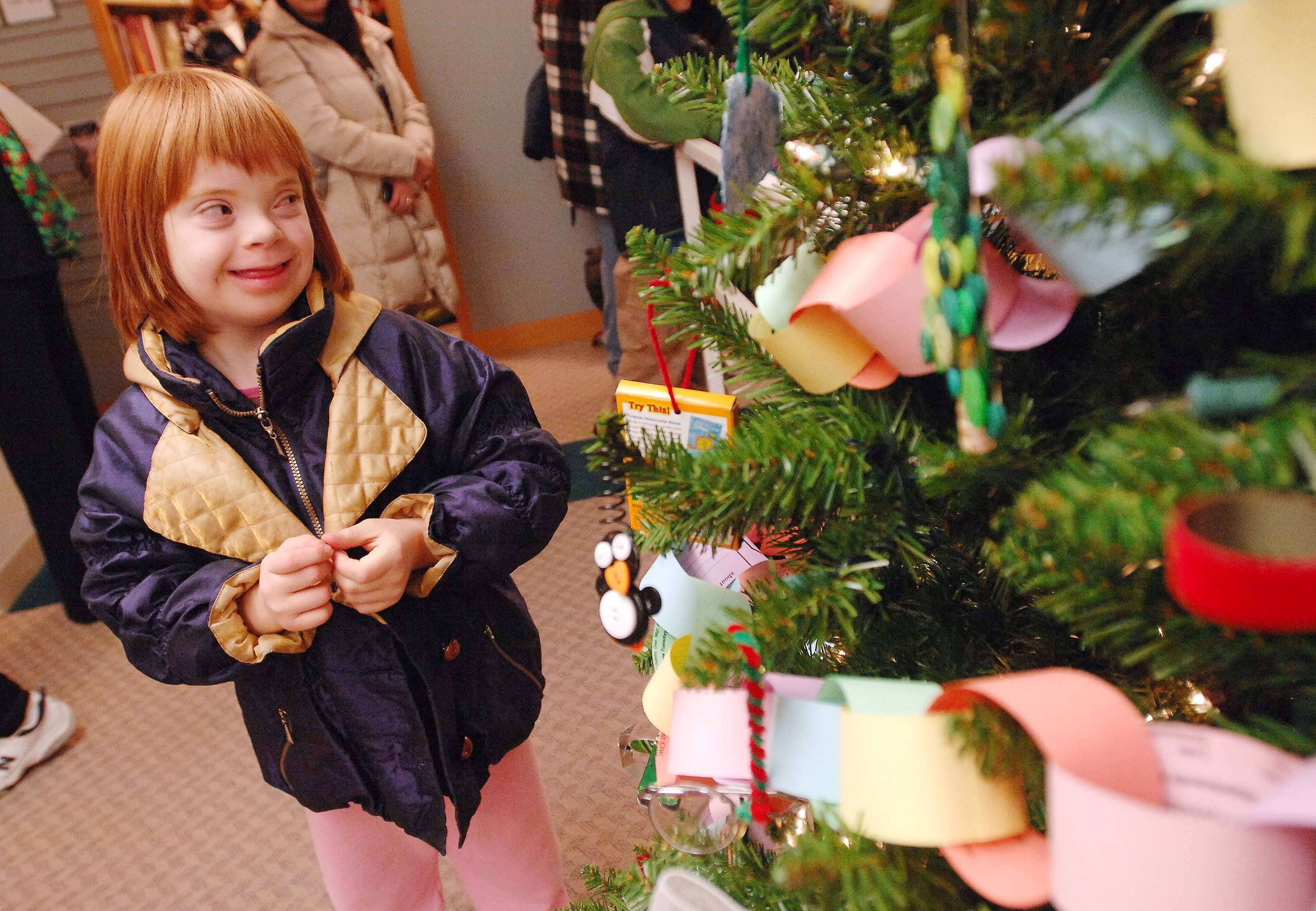 Hailey Casperson, 9, of Itasca looks at one of the 12 decorated trees on display during the Santa Comes to Town Christmas program at Itasca community Library Tuesday.