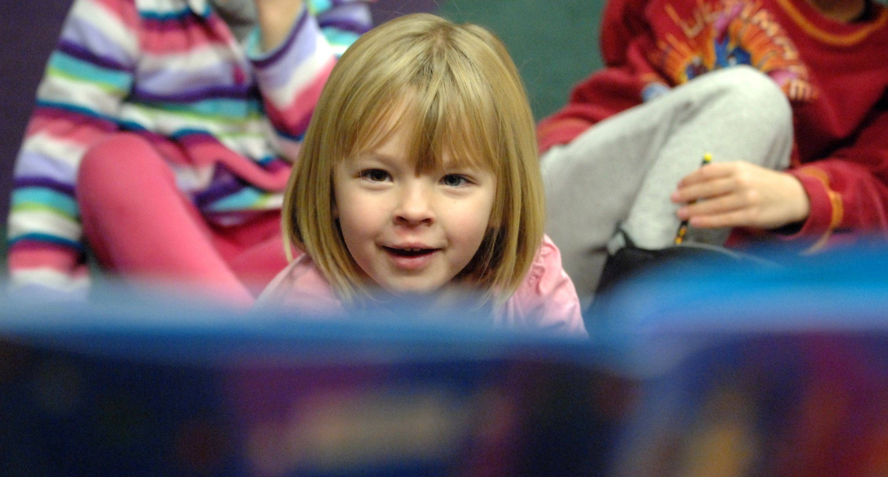 "Four-year-old Kathryn Danosky of Batavia listens intently to a reading of ""Snowmen at Christmas"" during holiday story time at the Batavia Library Wednesday."