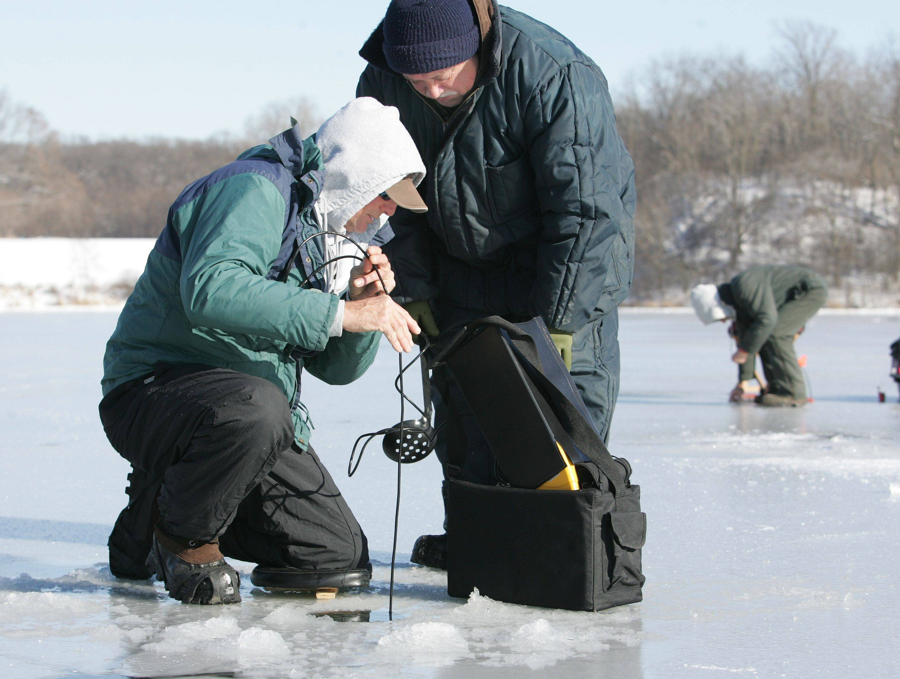Mike Martin of Batavia, left, and Jack Lapice of Romeoville use an underwater camera to locat the edge of the weed bed for the best ice fishing on Silver Lake in Blackwell Forest Preserve in Warrenville on Wednesday. Ice fishing has begun this week after the area's recent cold temperatures. The ice is currently about 4 inches thick.