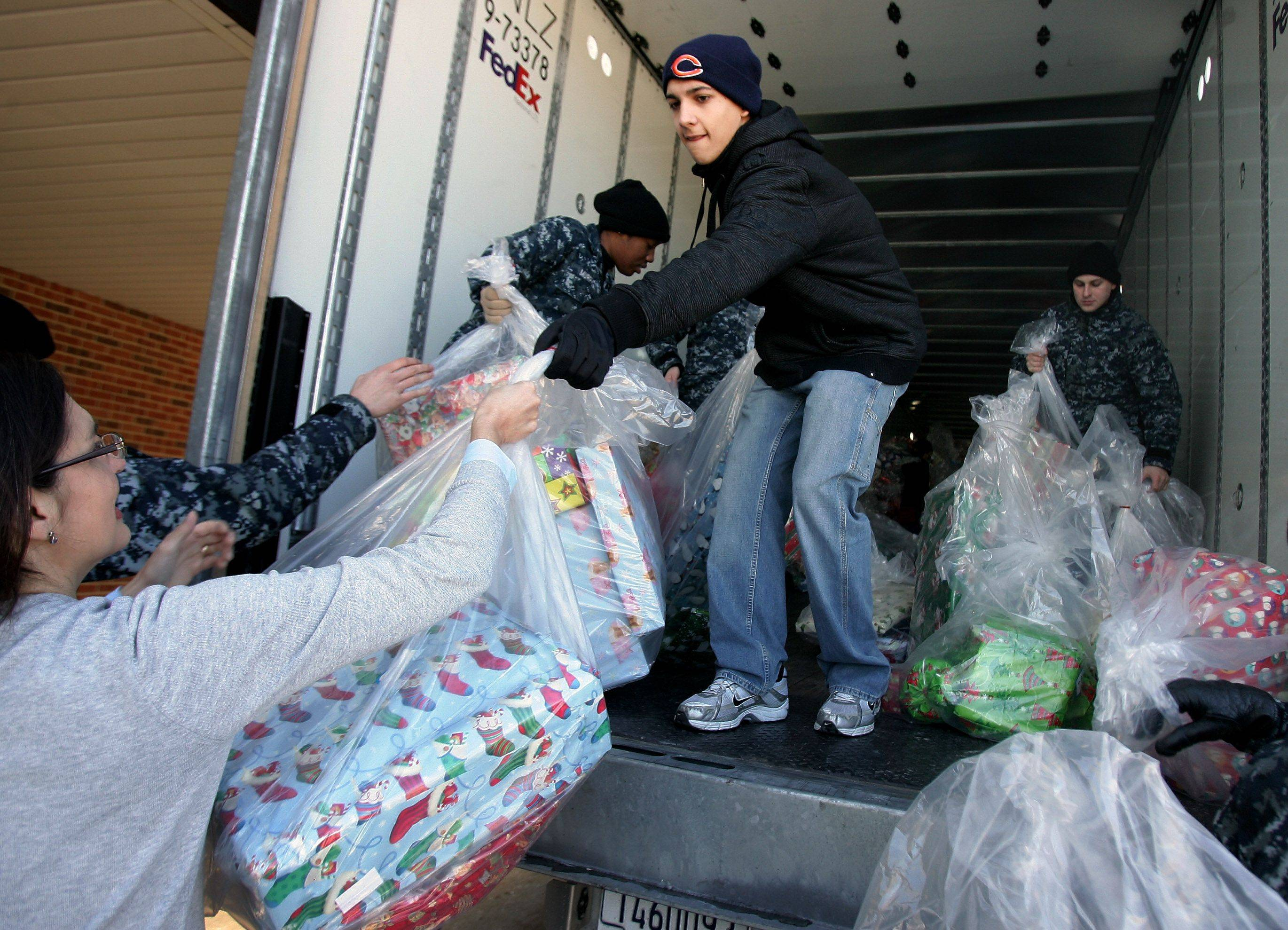 Eric Eiler, with the Stevenson High School National Honor Society, unloads toys that the school collected this past week as volunteers at Catholic Charities Lake County collect, sort, and distribute toys and clothes Wednesday at a storage facility in Waukegan. Catholic Charities hopes to deliver gifts to over 12,000 individuals for the holiday season. Sailors from Great Lakes Naval Base helped unload the gifts.
