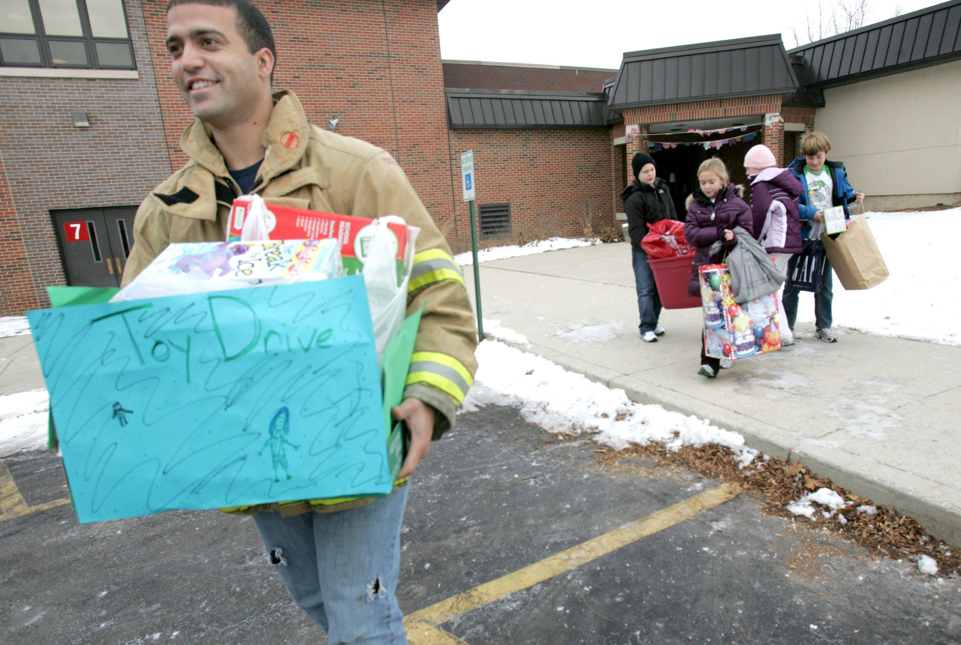 "Lombard firefighter/paramedic Josh Hays picks up toys from Pleasant Lane Elementary in Lombard. Left to right are student council members Thomas Batka, Josilin Johnson, Alexis Weltin, and Avyn Alairys helping bring out the toys. The toys will be taken in the toy parade on Saturday to Yorktown Center, where they will then be part of the toy drive. ""I think it's going to a good cause"", said fifth-grader Joslin Johnson, president of the student council. All members of the student council agreed it's better to give the toys to charity, then having them sit around at home unused. The school collected over 100 books and toys for the drive this year."