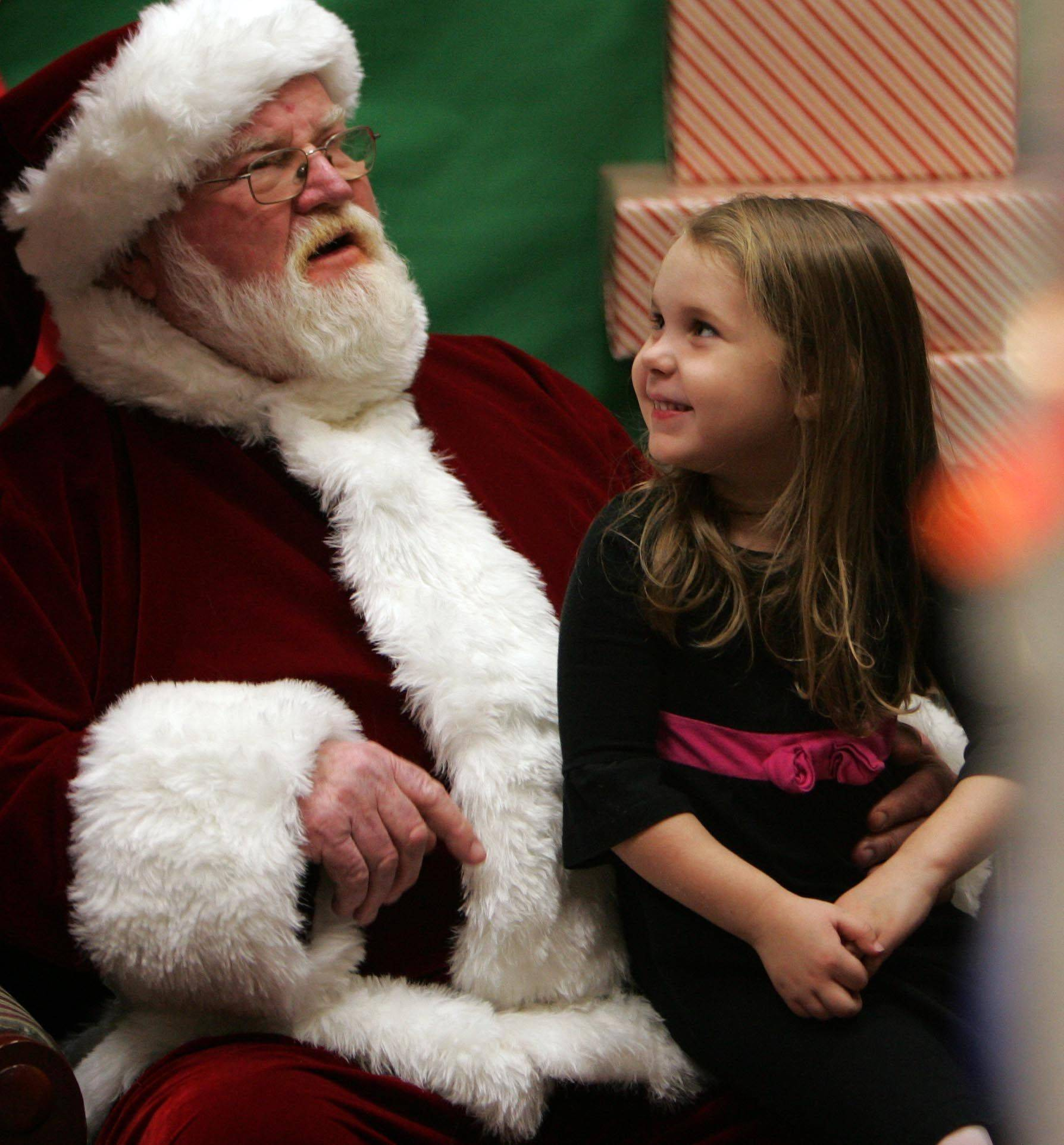 Six-year-old Sydney Warford of Elburn passes her wish list on to Santa as he visits the Town and Country Library in Elburn Friday, December 3.