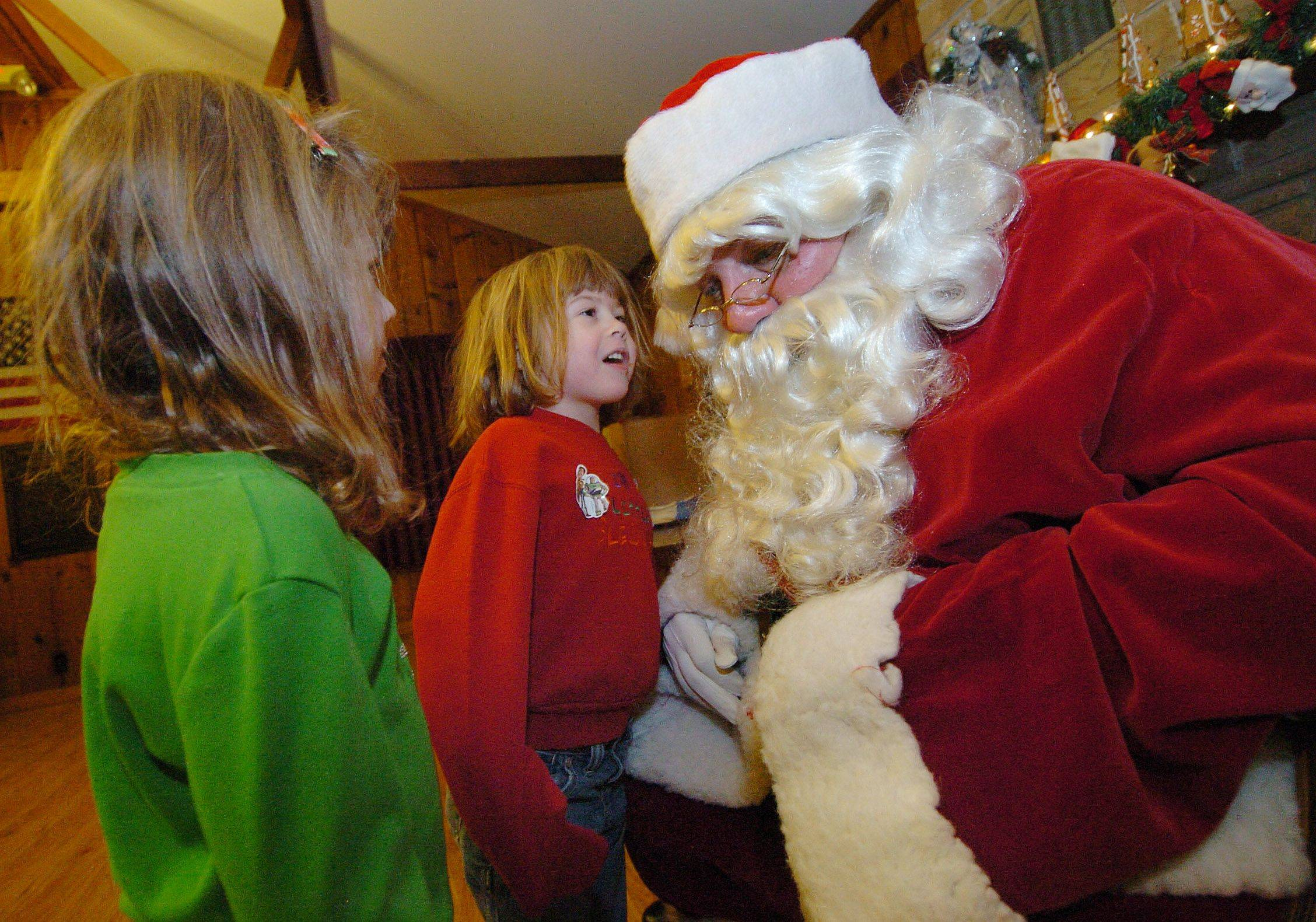 Twin sisters Anna, left, and Emily Nauman whisper to Santa what they want for Christmas in the log cabin prior to the Christmas tree lighting in Bartlett Park.