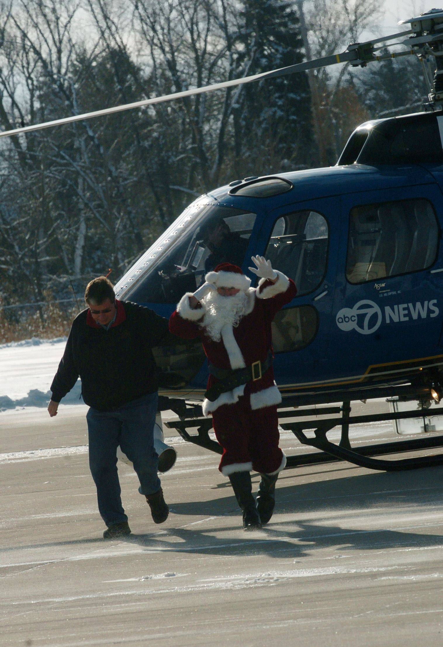 Santa waves to the families waiting for him at Schaumburg Regional Airport's hangar Sunday morning after flying in on ABC 7's helicopter.