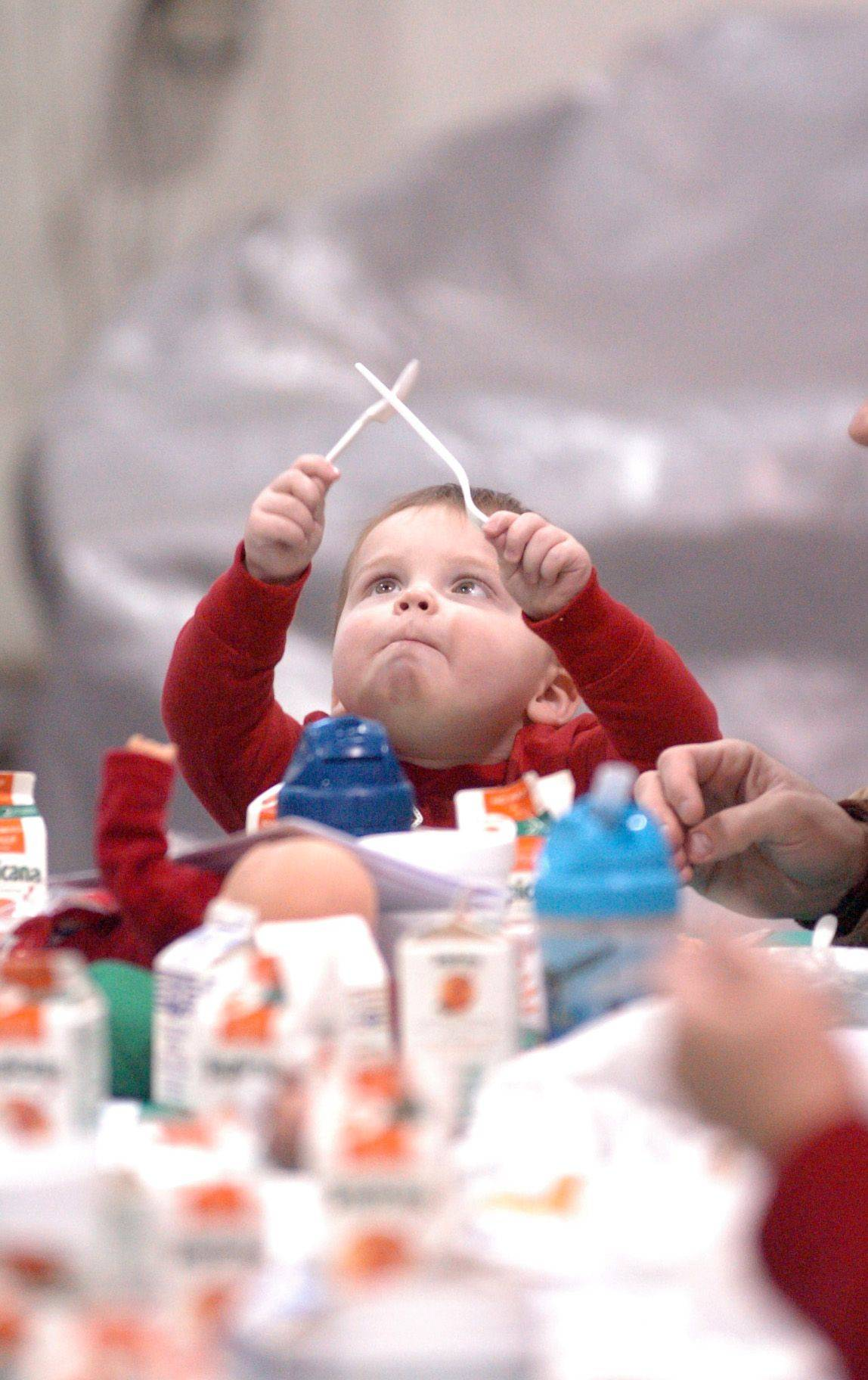Michael Goolish, 1, from Schaumburg plays with his eating utensils during breakfast while waiting for Santa's arrival at Schaumburg Regional Airport Sunday morning.