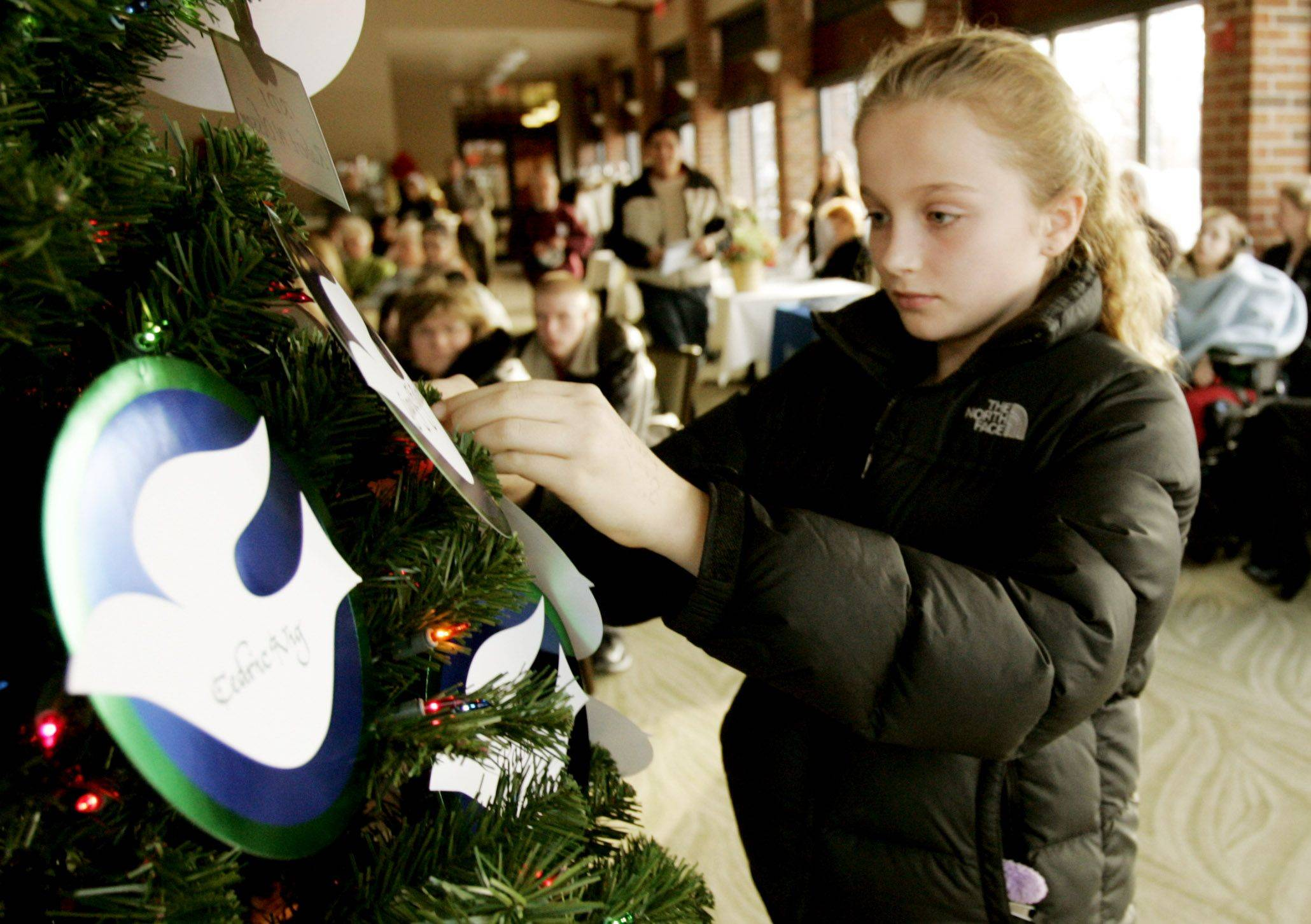 "Katherine Kuzas, 10, of Chicago hangs ornaments on the Tree of Lights Sunday in a memory of her grandpa ""Opa"" at Cantigny Park in Winfield."